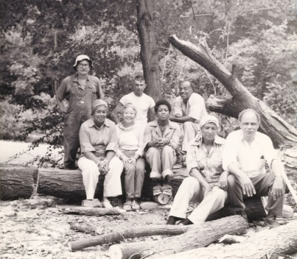 Constance Baker Motley and husband Joel seated far right on log, clearing a fallen tree from their Chester land off Cedar Lake Rd. At left (standing) is Tom Stieger, Dan Agnelli, and David Green, husband of Constance Motley's sister Marion Baker Green (seated left), beside Pat Stieger (Tom's wife) and unidentified woman. Circa 1975.