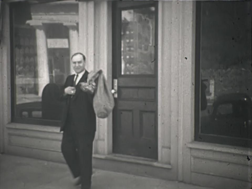 Jim Grote, Chester postmaster, in front of the post office, then at 1 Main Street. From the 1930s film