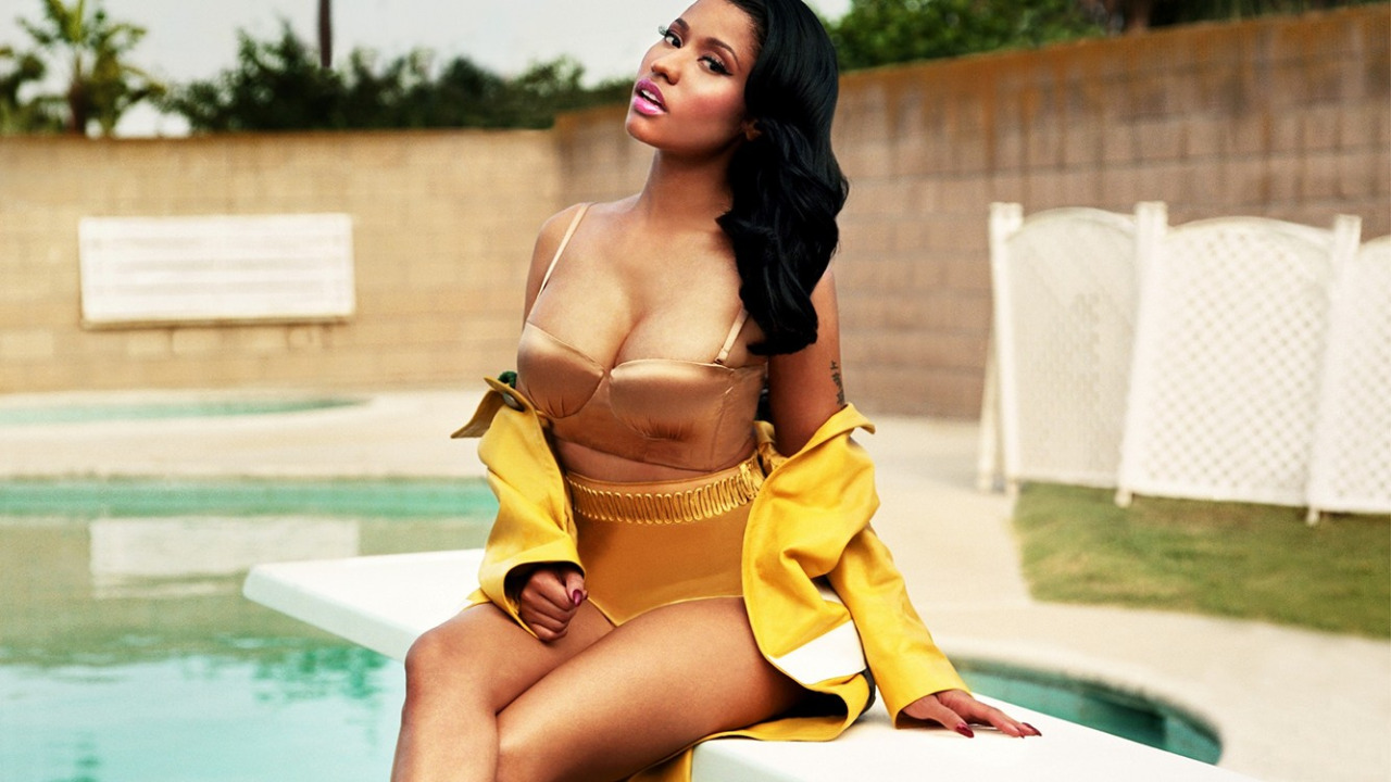 """In a manicured cul-de-sac in LA's Baldwin Hills, Nicki Minaj's matte black Maybach lurks in the shimmering heat – doors flung open to let the still air circulate and privacy curtains pulled back.  The $500,000 car cuts an imposing silhouette against the mid-century home where its owner is posing for today's shoot. In the driveway, her personal chauffeur, bodyguard and day-to-day manager keep watch, hovering patiently while Minaj acts the suburban housewife inside.    Ripping off yellow rubber gloves in order to slip into a Balmain two-piece, Minaj insists the scenario isn't quite the American daydream that it seems. """"I'm in a surreal world, but I'm so normal in it,"""" she says, striding across the yard in gold Giuseppe Zanotti heels. """"Most people that I know in the industry have maids, housekeepers, ten bodyguards and a masseuse with them at all times. Everyone around me is like, 'You're so much more low-key than I thought!' But I don't like going out, I don't like crowds, I don't like clubs. If I do have downtime, I prefer to be in the house cooking West Indian food and watching my DVR.""""    After a few hours of tense outfit changes, the 31-year-old heads back to her trailer to unwind after a day playing a hyperreal homemaker. In person, she has a presence that belies her tiny 5'2"""" frame, giving off a vibe of steely authority that hums louder than the trailer's aircon. Curled up on a paisley couch, brushing out her demure Veronica Lake waves, Minaj says she has every intention to """"stop what I'm doing and be a mother and wife. But not yet."""" Before she can settle down to a life of quiet domesticity, Minaj wants to release five albums in total. """"I have to make 500 million dollars first,"""" she says. """"That figure has been in my brain for a long time. I want to be the female who earned the same amount of money that the Jay Zs and the Puffys were able to earn. I feel like when I reach my 500-million-dollar goal"""" – she pauses to cackle at the Monopoly-money sum, teeth bared – """
