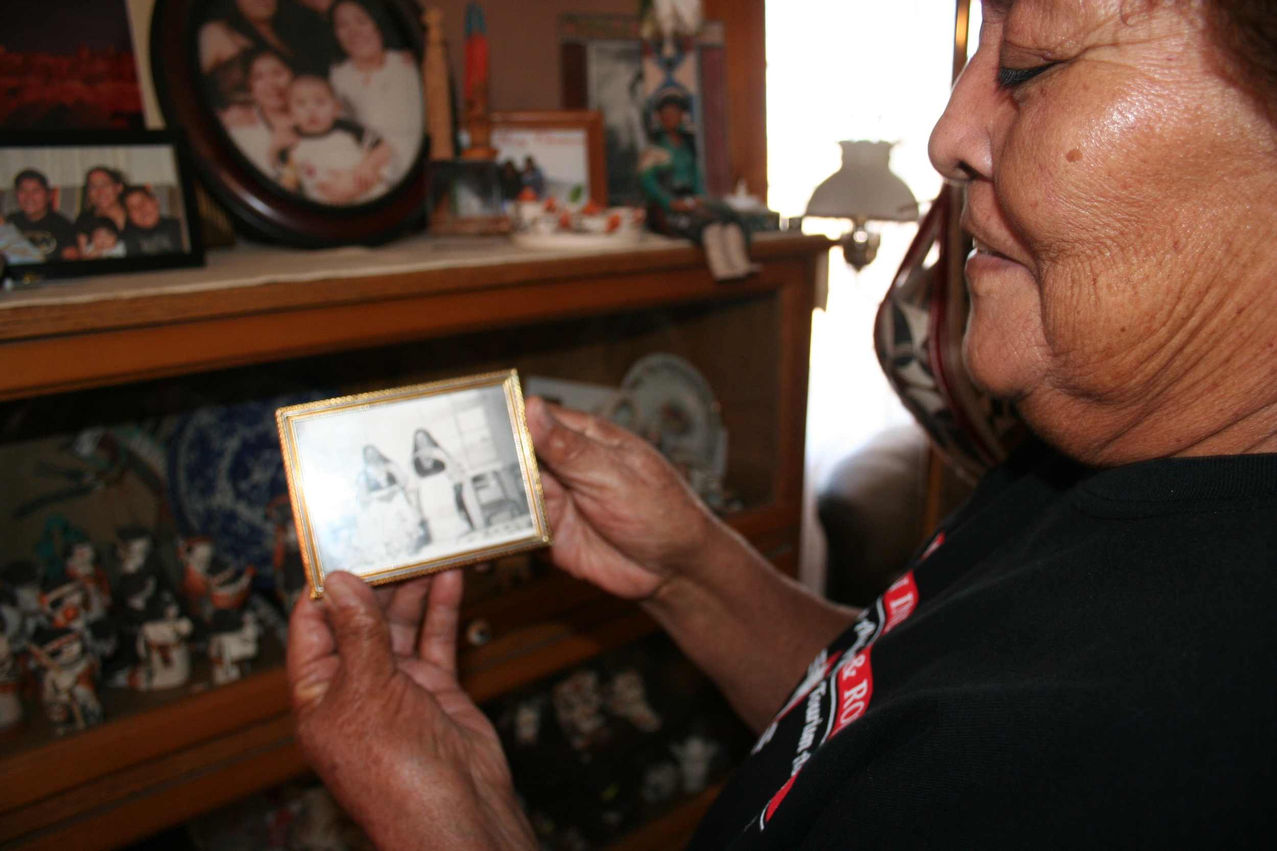 Acoma elder Mary Lowden holds a photo of her mother and her aunt, both pottery makers.