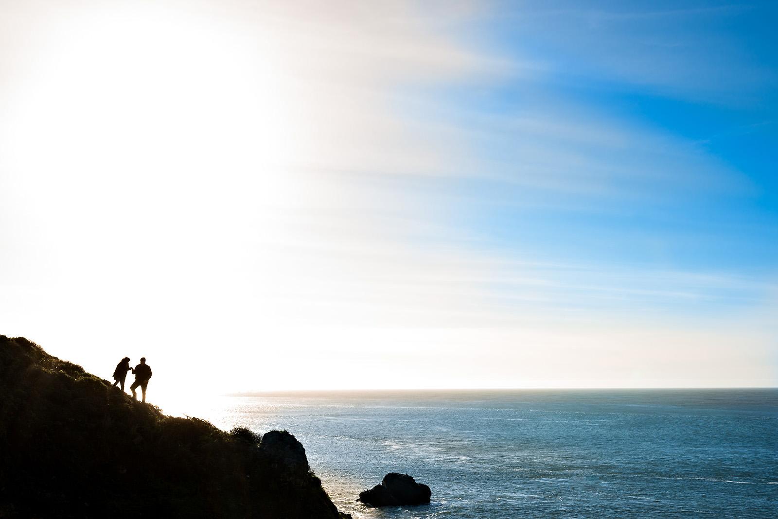 couple-climbing-cliff-over-ocean