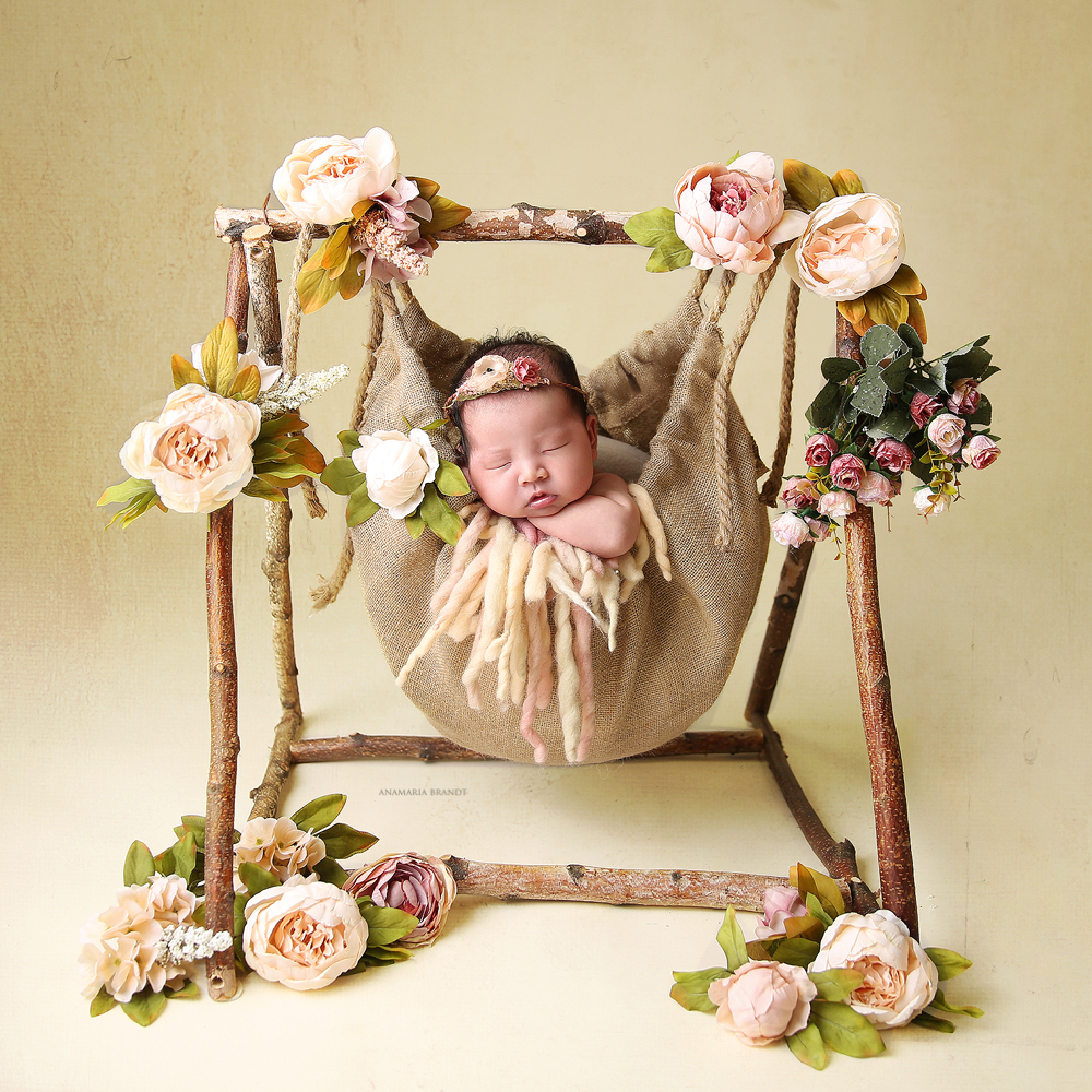 Newborn-in-burlap-swing-surrounded-by-flowers