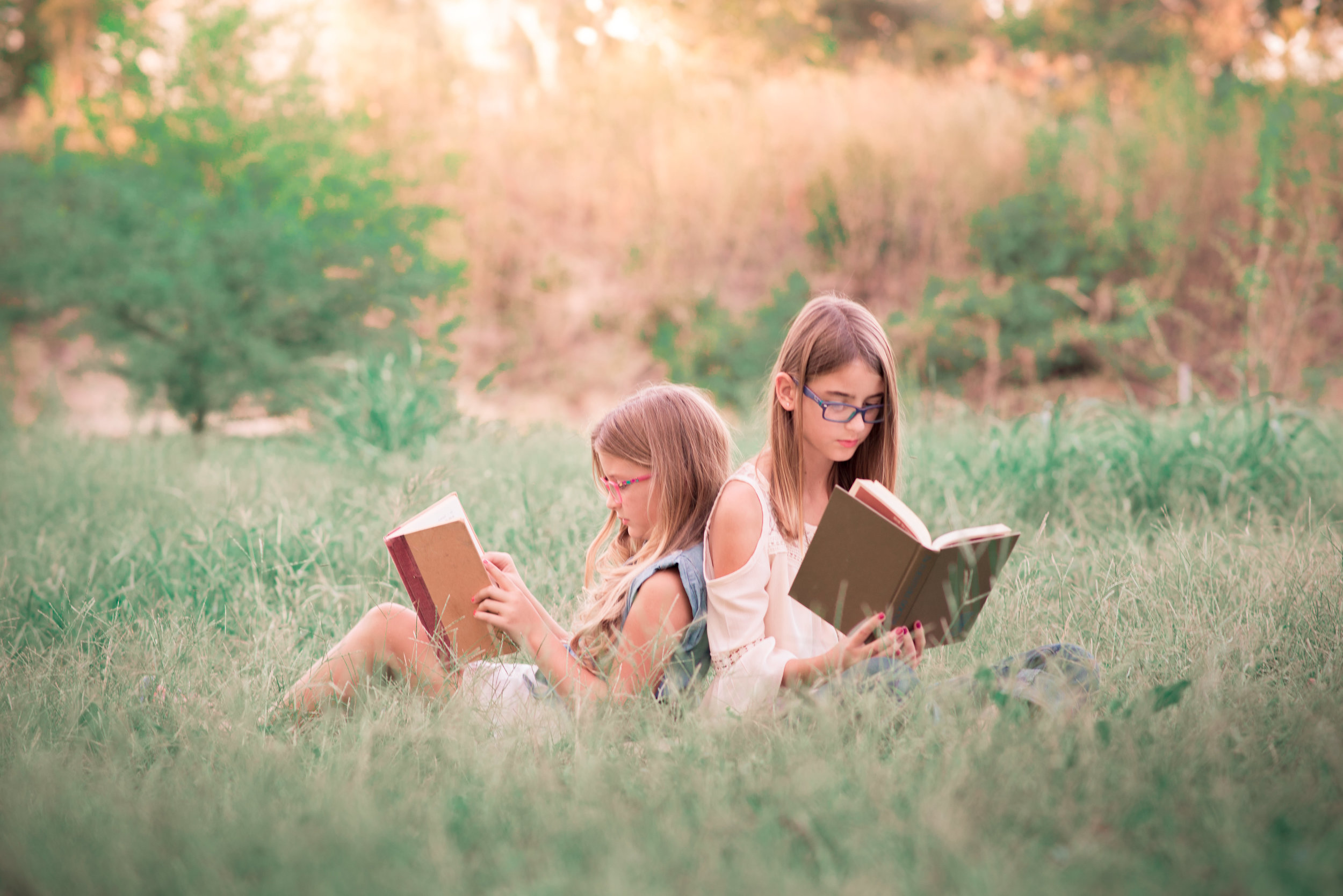 two-young-girls-reading-books-in-a-field