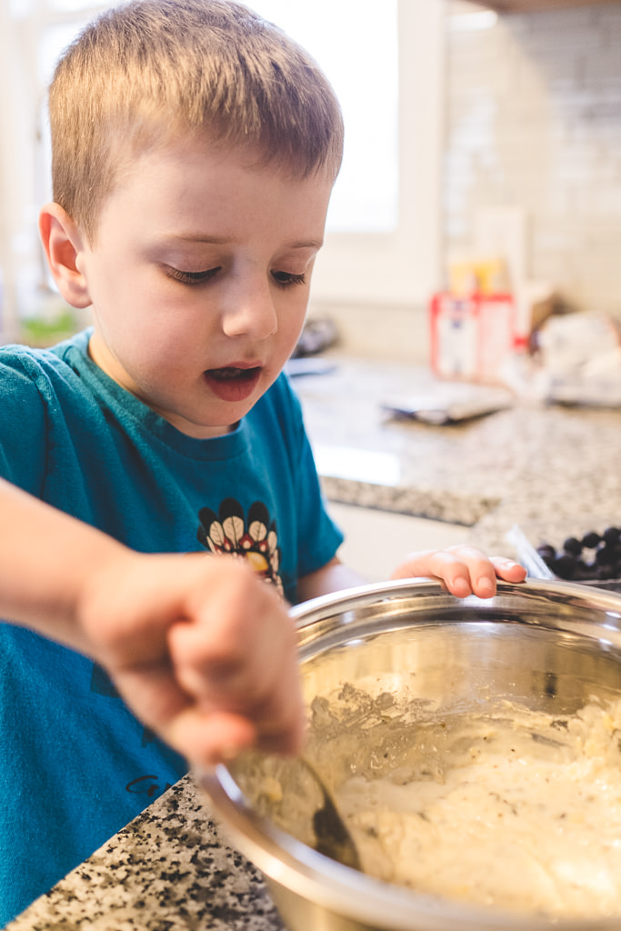 child mixing muffin mix in bowl