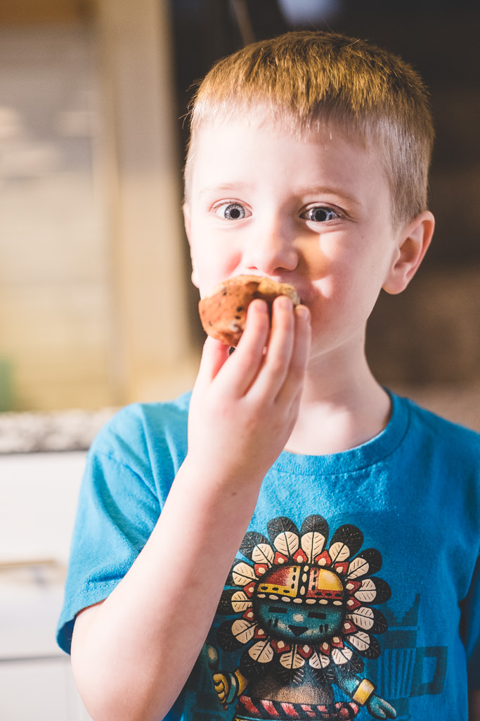 young boy eating a fresh blueberry muffin
