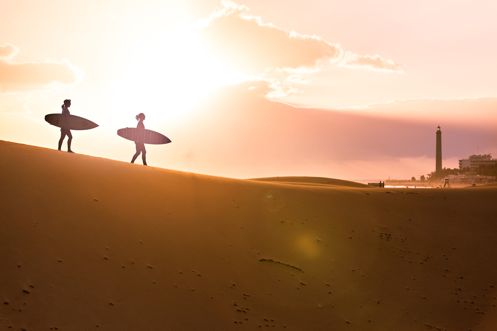 two-surfers-walking-to-beach-at-sunrise