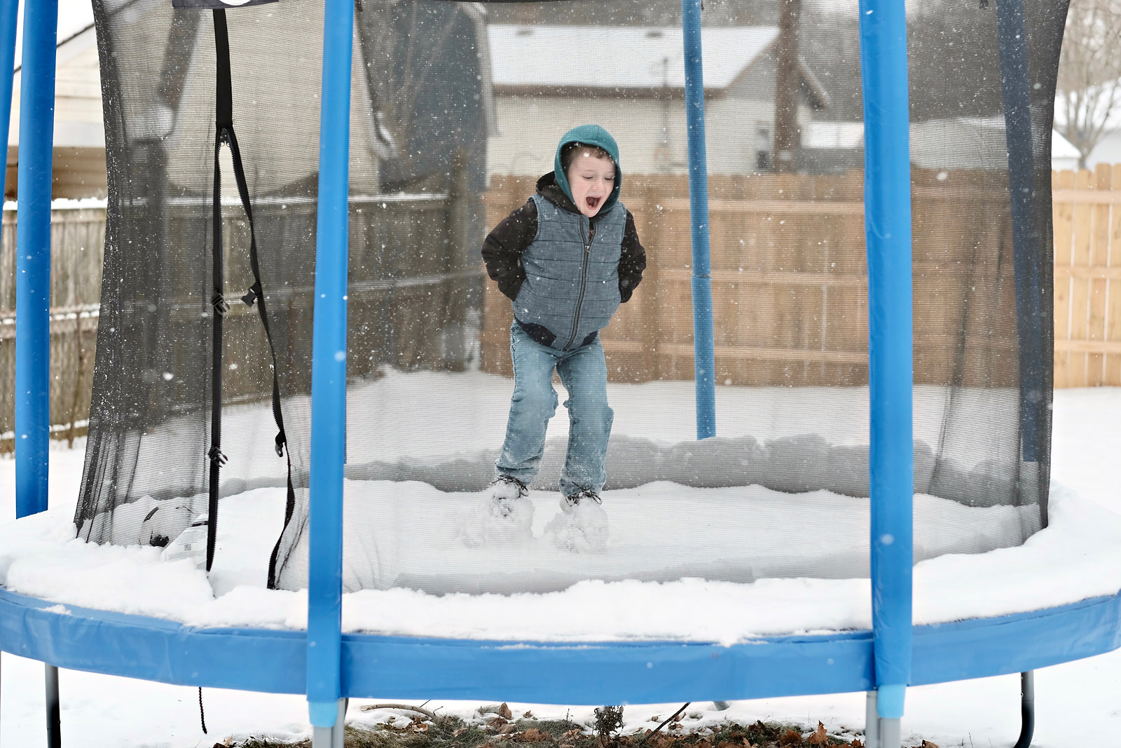 boy-jumping-aroung-snow-covered-trampoline