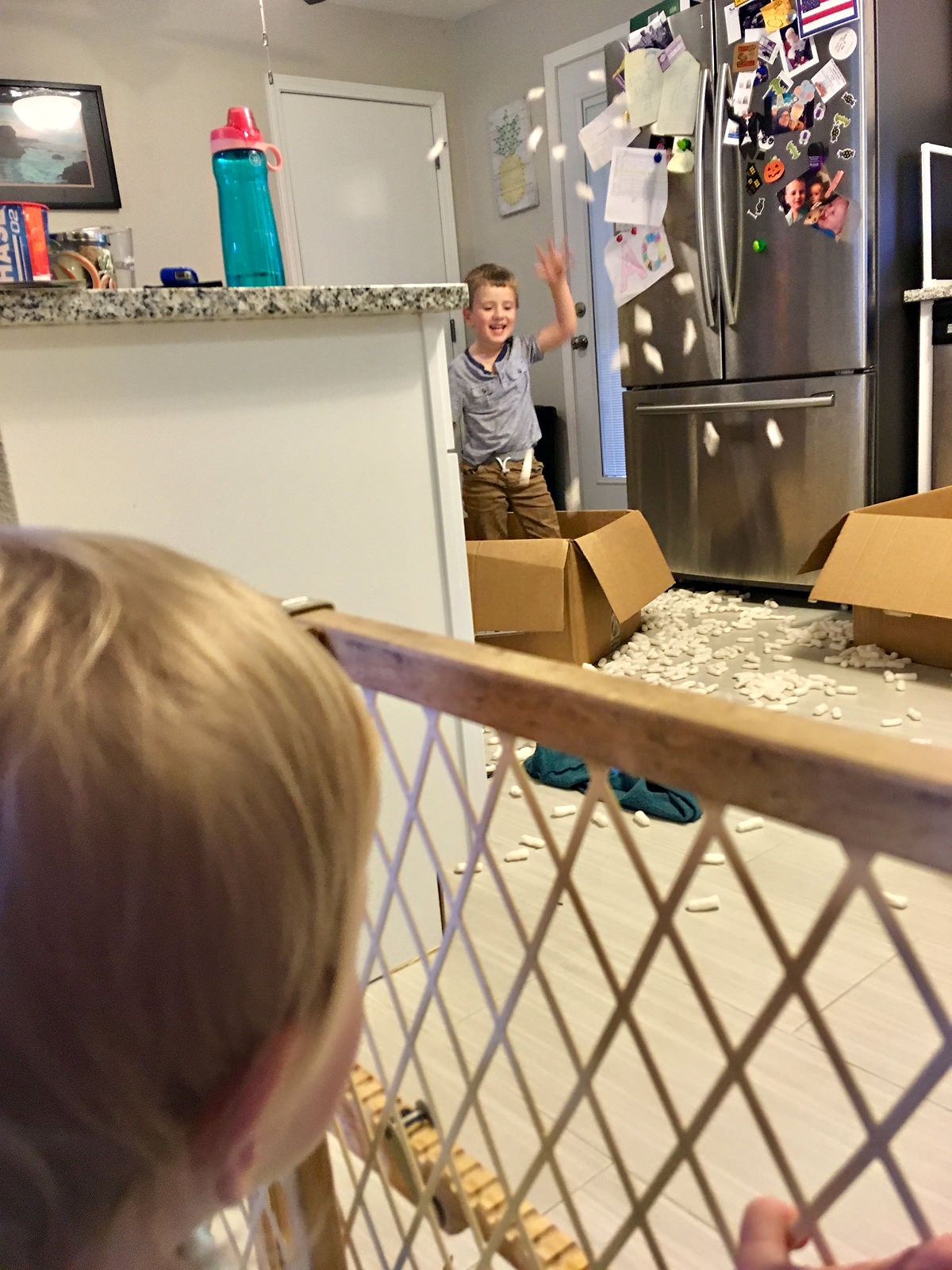 boy-throwing-packing-peanuts-all-over-white-kitchen