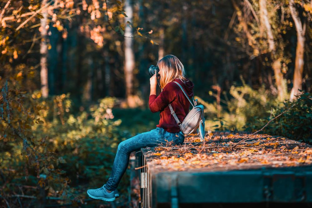 blonde girl using camera in forest by David Bartus.jpg