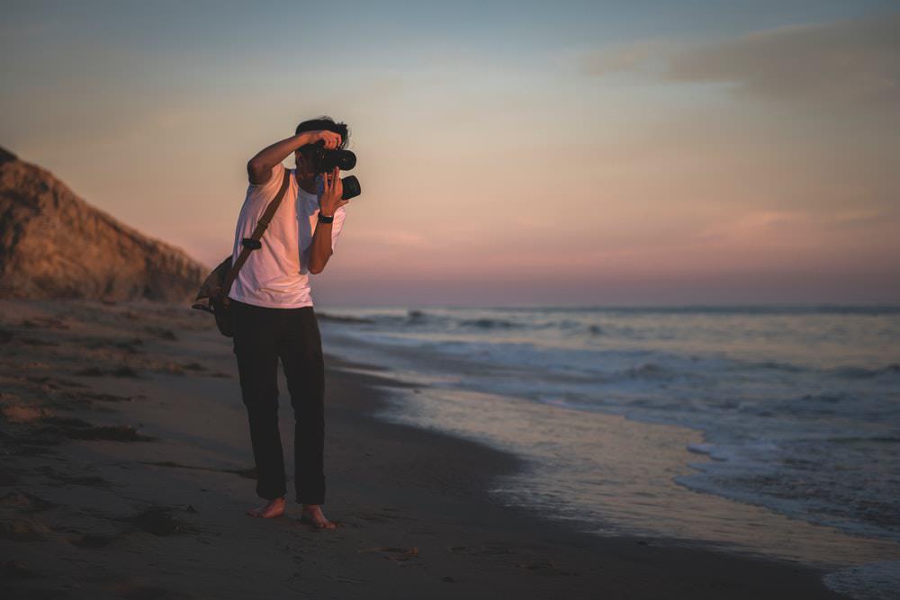man walking on beach taking photos by Tim Mossholder.jpg