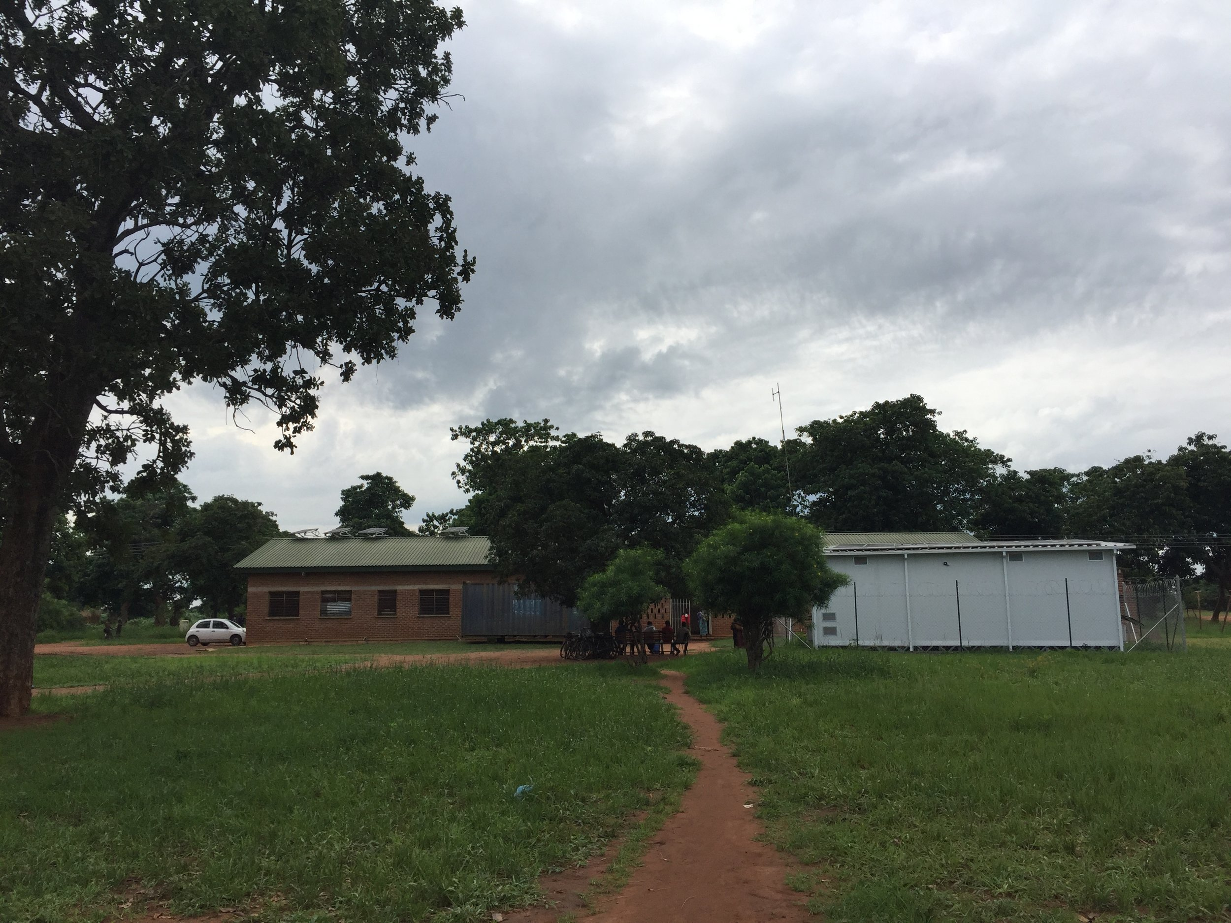 Malembo Rural Health Center (brick building on left) and cold storage pharmacy (white structure on right).