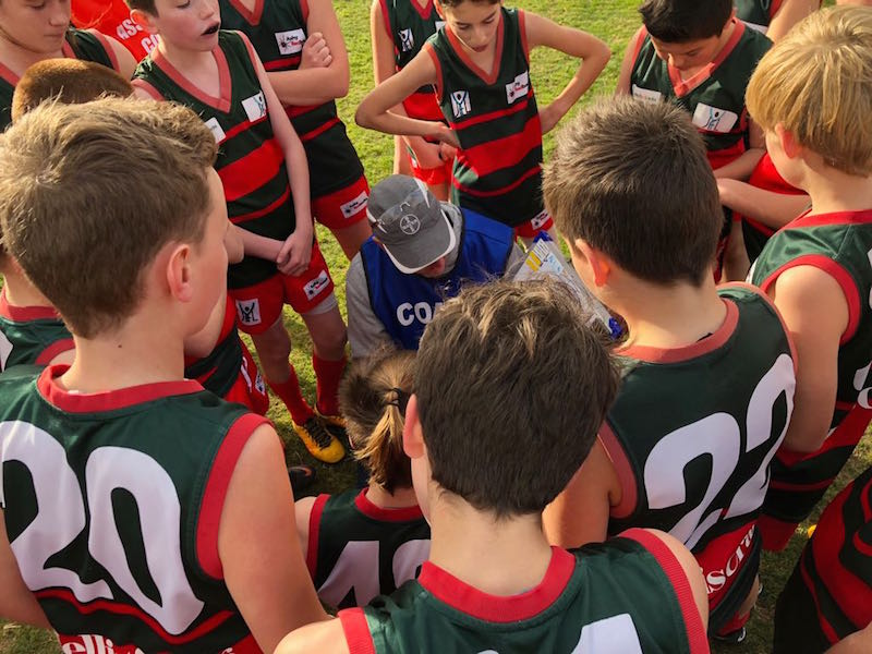 Ecogroup U13 Green huddle in close to listen to their coach, Leigh's instructions.