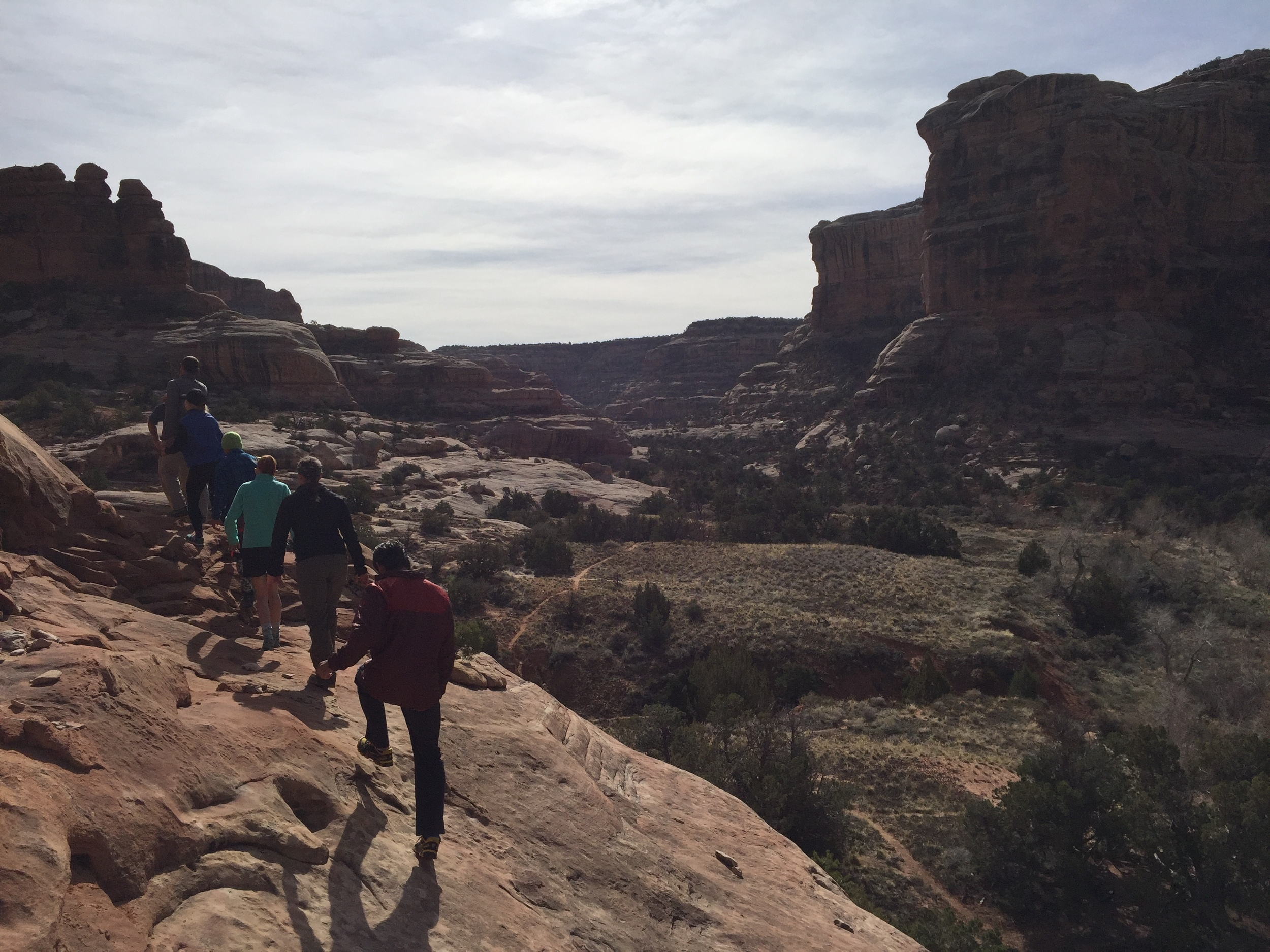 Link students scramble across a ledge leading to Perfect Kiva, high along the canyon wall