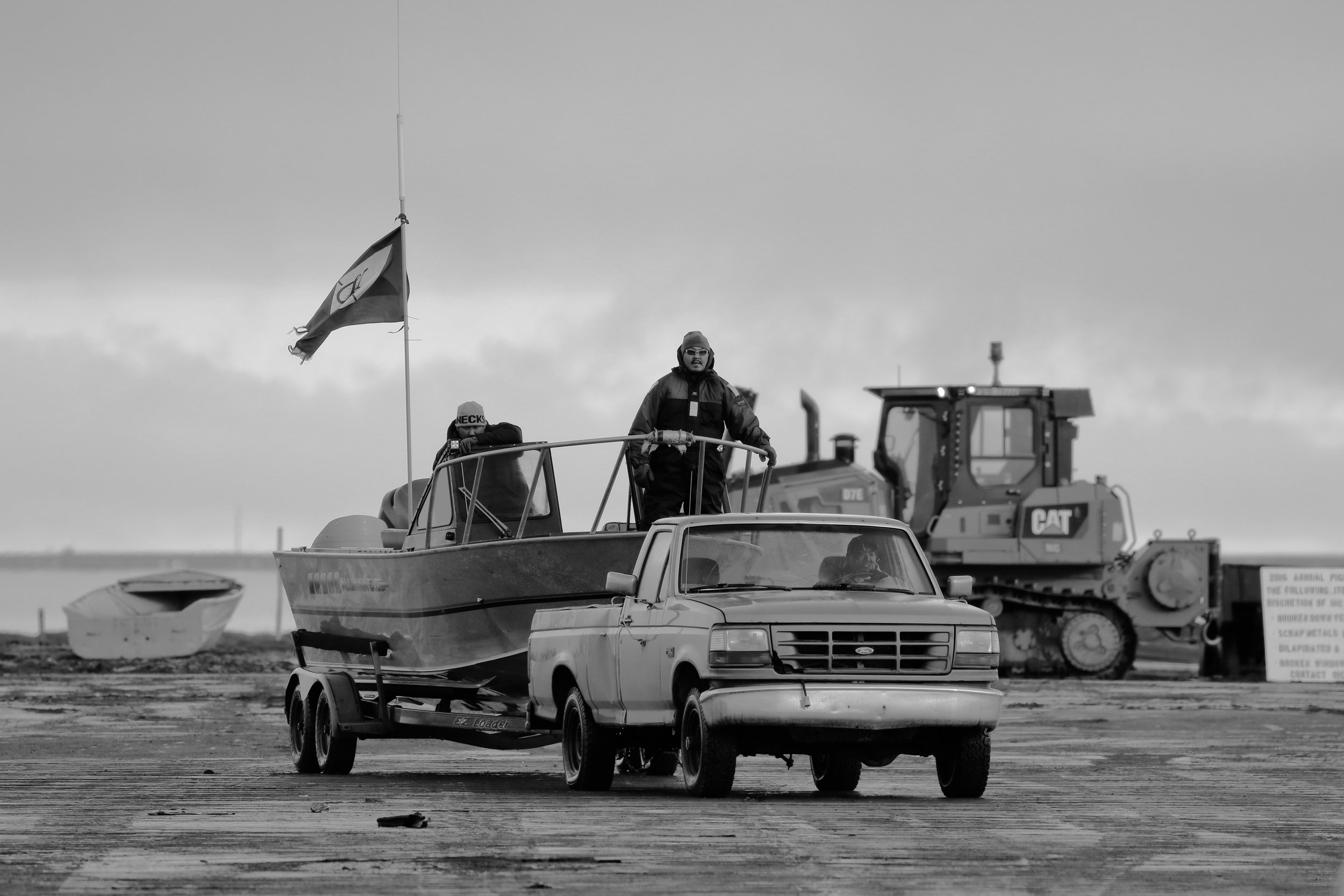 The Captain of the successful whaling crew returns from the ocean with their flag proudly displayed.