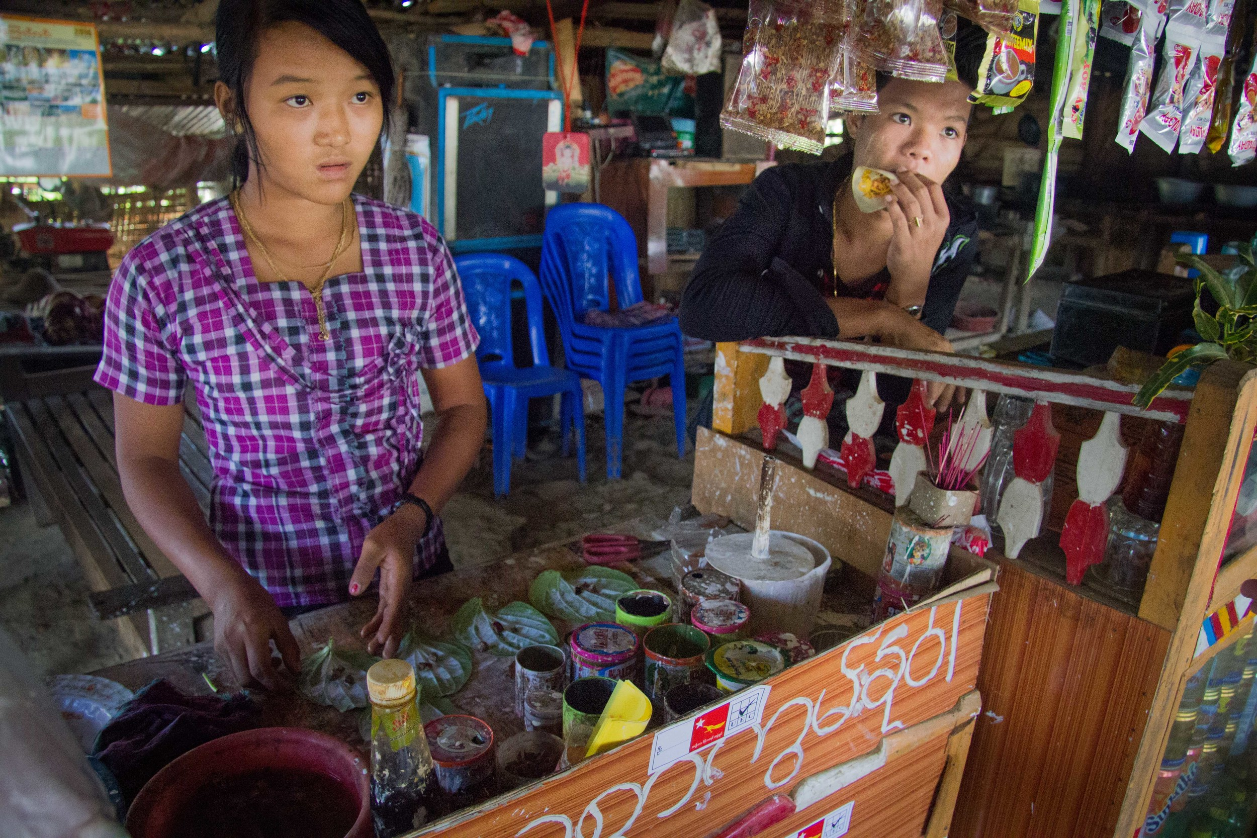 A girl concocts some betel leaves with tobacco and flavouring for a customer