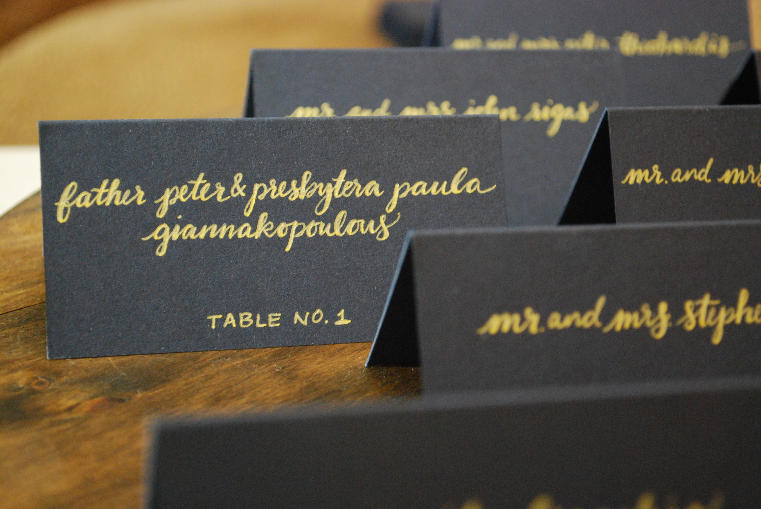 Tented navy blue escort cards with gold script