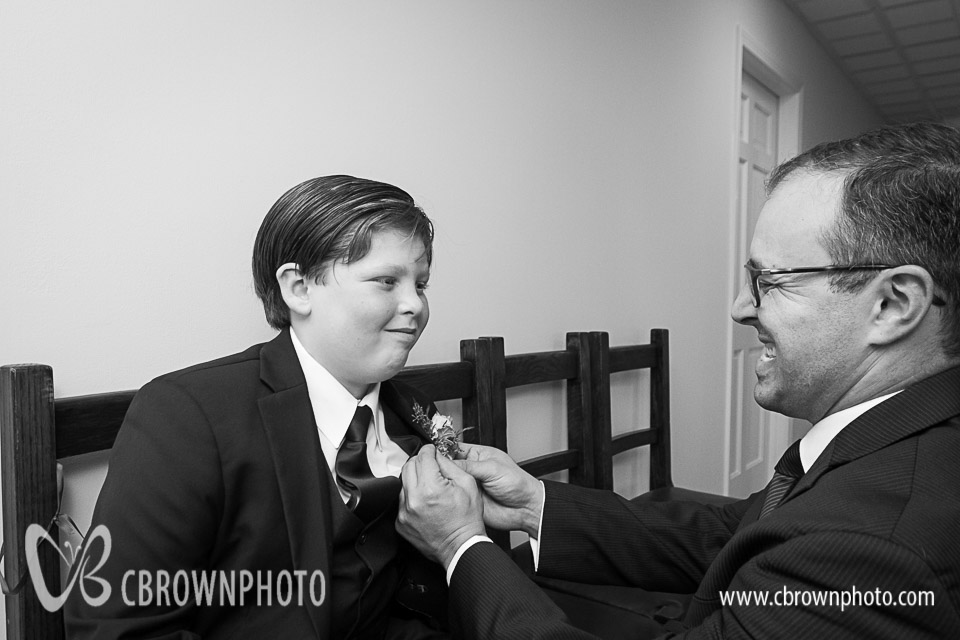 Nem helps Rachael's son Aiden, the ring bearer, with his Boutonnier.