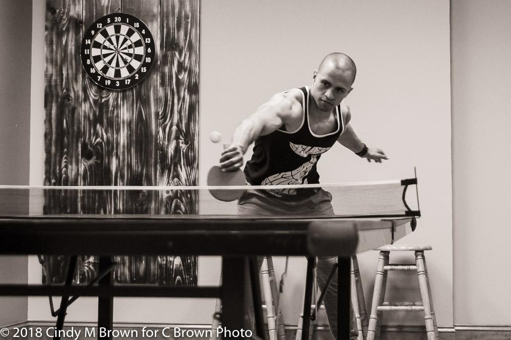 The groomsmen play ping pong.