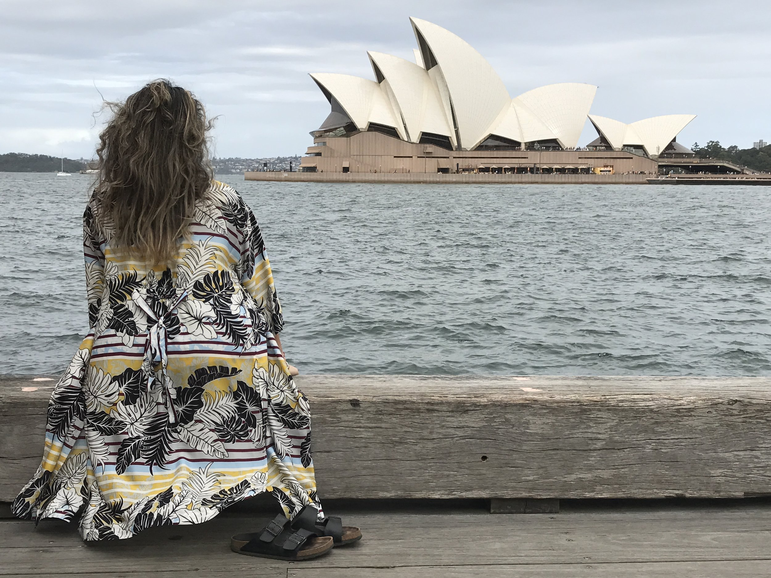 The breeze catching my long jacket as I sit and take in the Sydney Opera House on a cloudy day