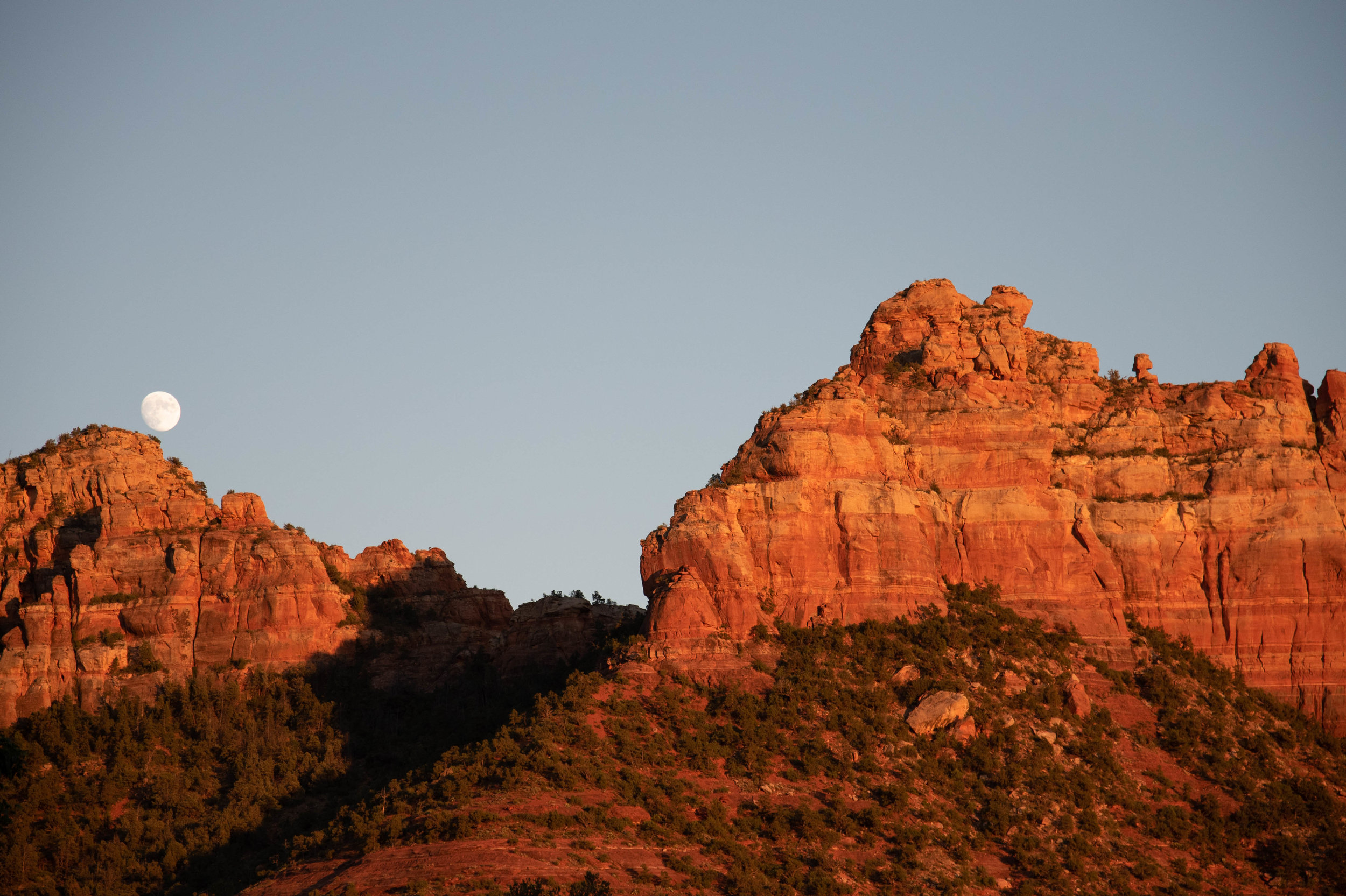 Moon rising at sunset over red rocks