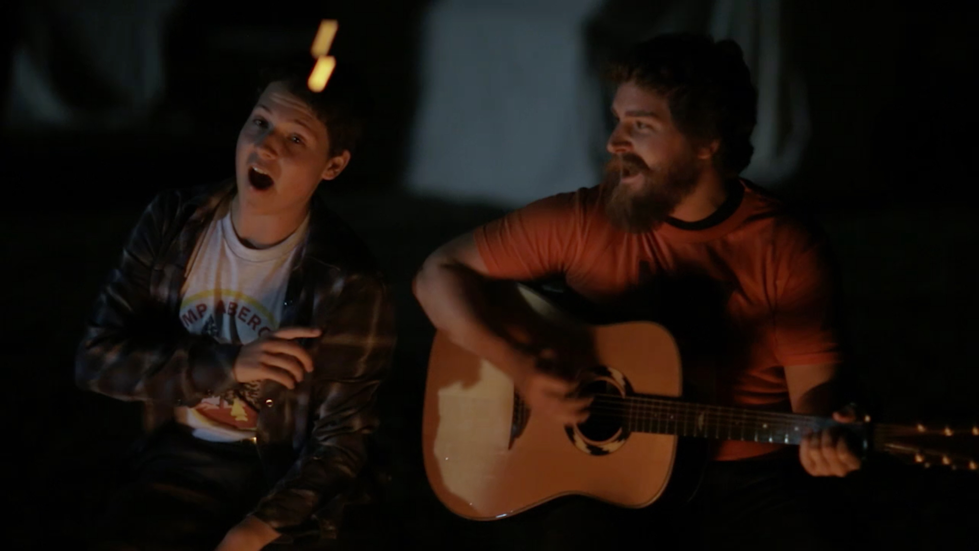 Jeff Rosick and Zach Louis sing around the campfire.