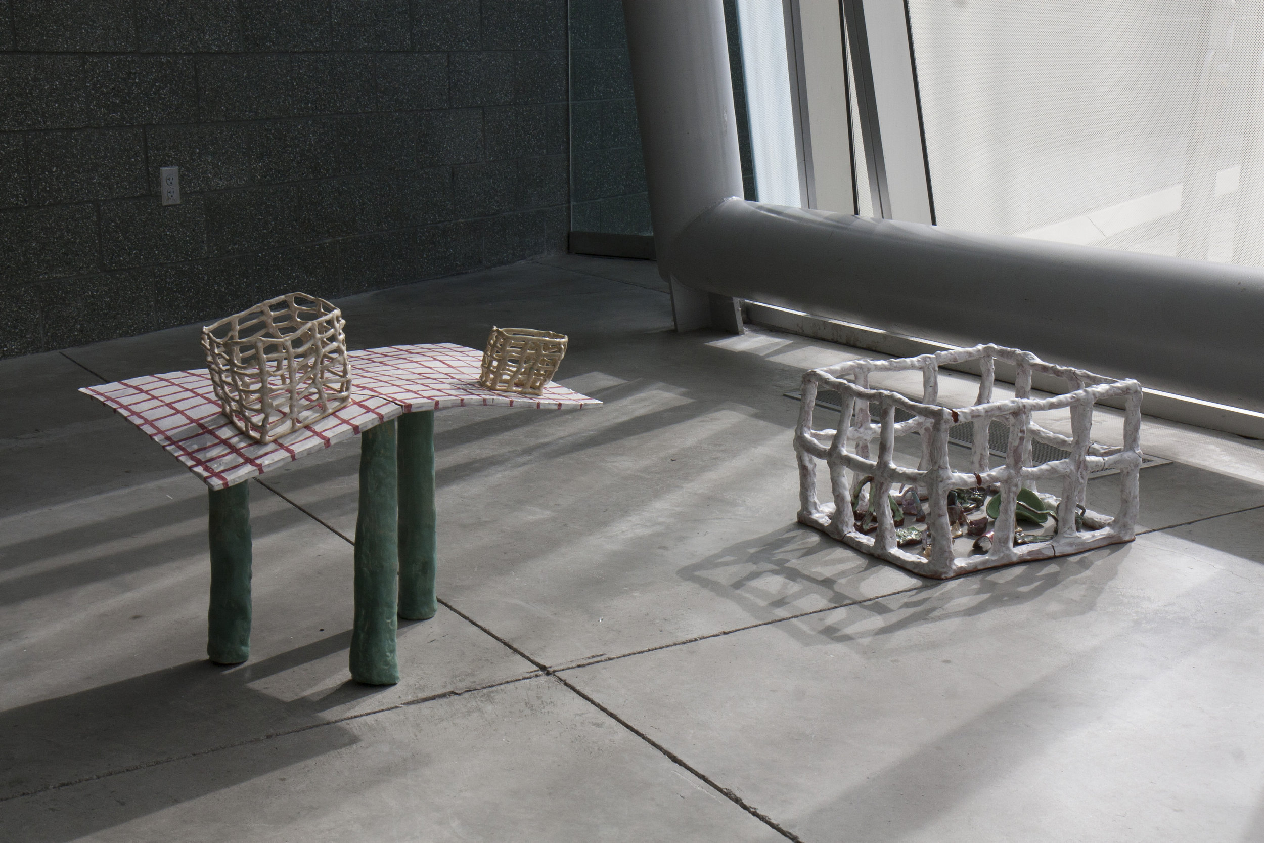 """playroom invitation  2017 ceramics table 1.5x1.5x2.5"""" cage 1.5x1x2.5"""" objects are roughly palm sized   bringing objects from my dreams into existence  participants were invited to play and construct their own reality under observation in a sterile environment"""