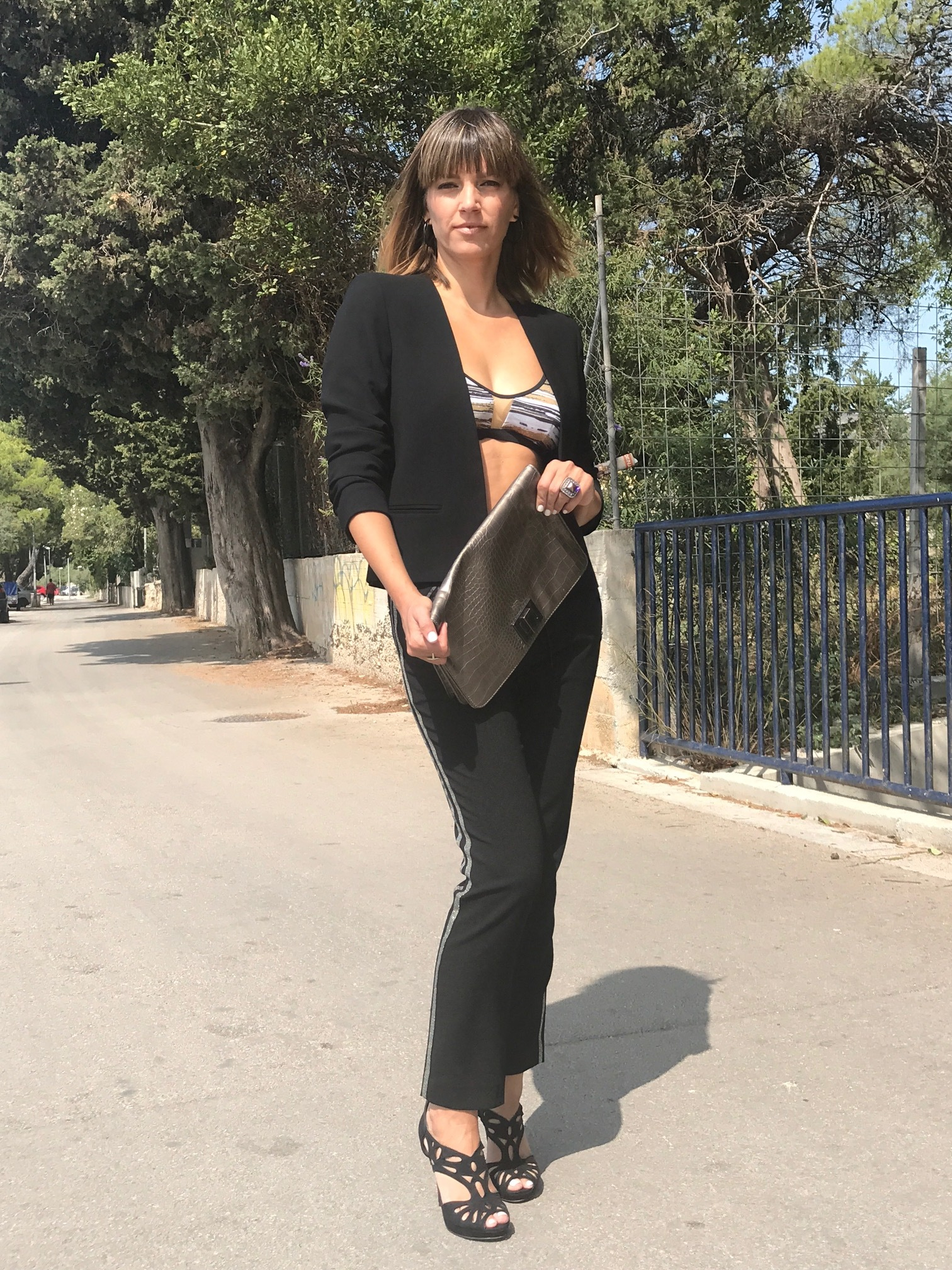 Black pants with golden stripes, black blazer, black and golden bikini top, black heels, golden bag
