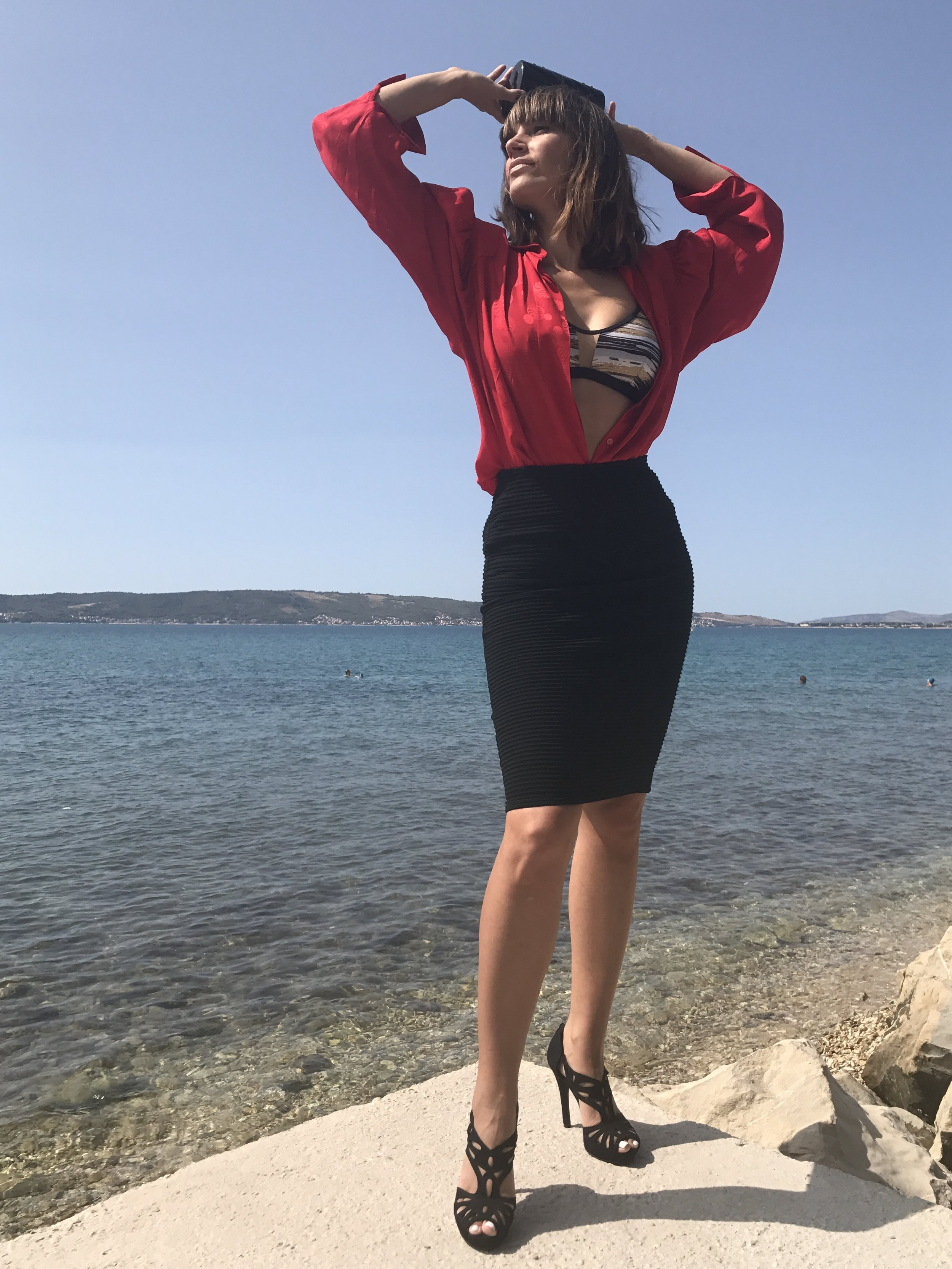Black pencil skirt, black and golden bikini top and red blouse tucked in the skirt open in front, black high heels, black clutch
