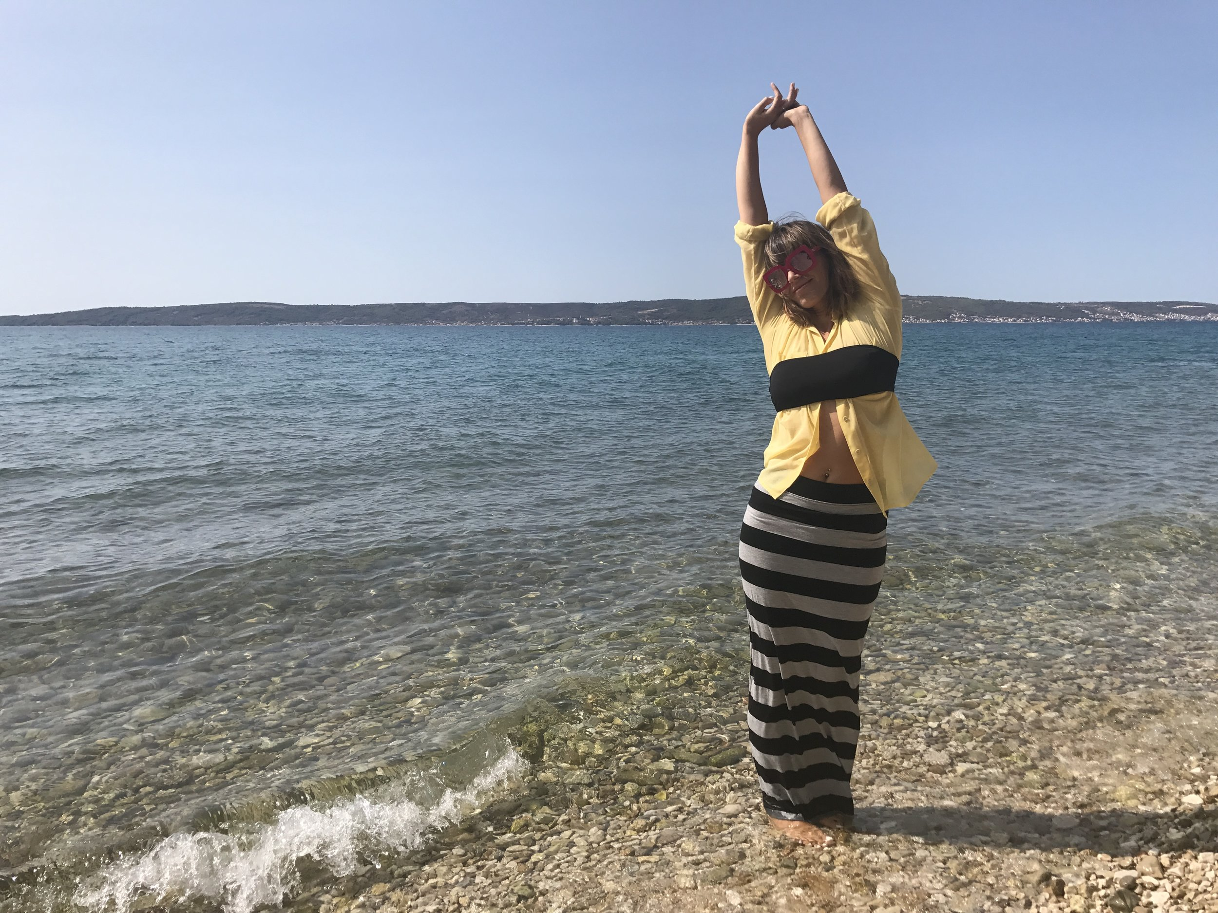 Black bikini top over transparent yellow blouse and striped grey and black maxi skirt