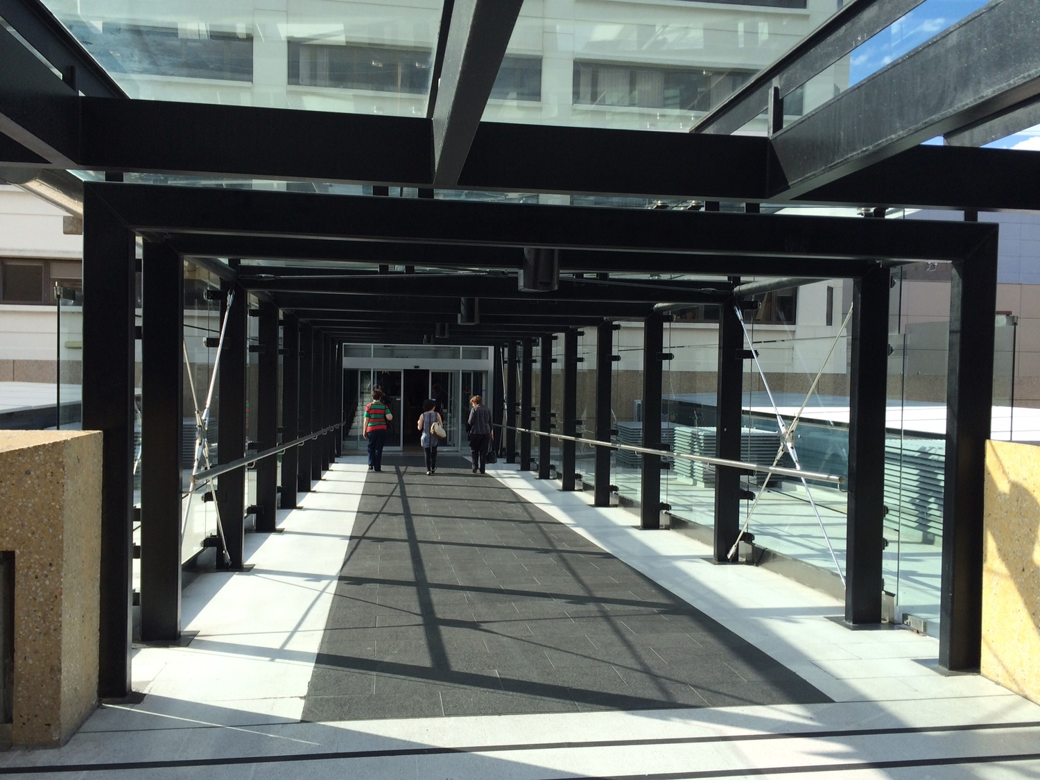 Use Sky Bridge located on Level 1 of Roof Top Car Park.  Proceed down Corridor.