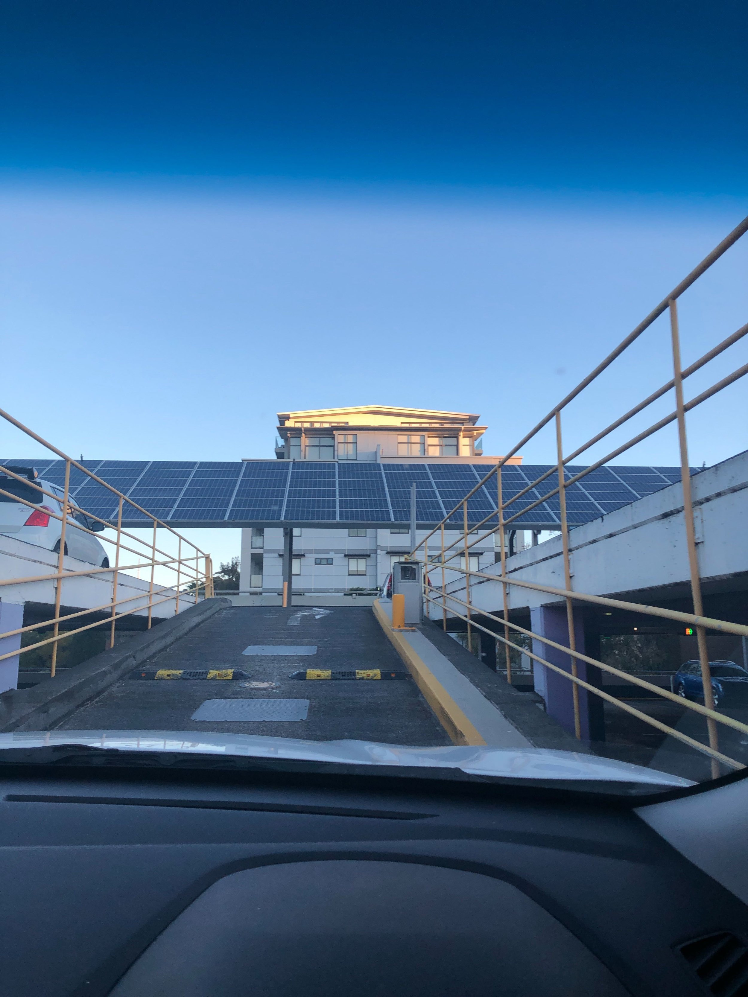 Continue on up the ramps until you see rooftop parking with the satellites. Turn Right and immediately Turn Right again.