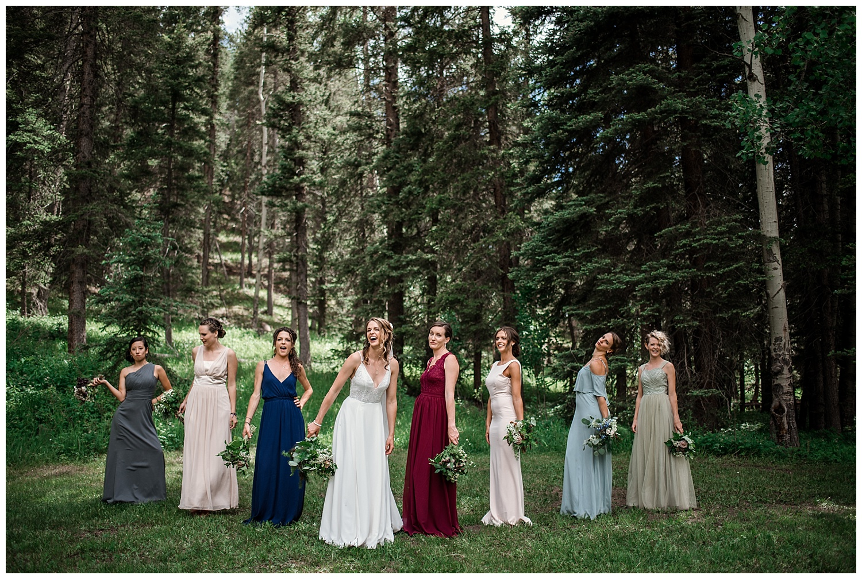wedding party portraits at Beaver Ranch in Conifer Colorado, Colorado Wedding Photographer, Rocky Mountain Wedding Photographer, Intimate Colorado Wedding Photographer, bridesmaids laughing in jewel toned dresses