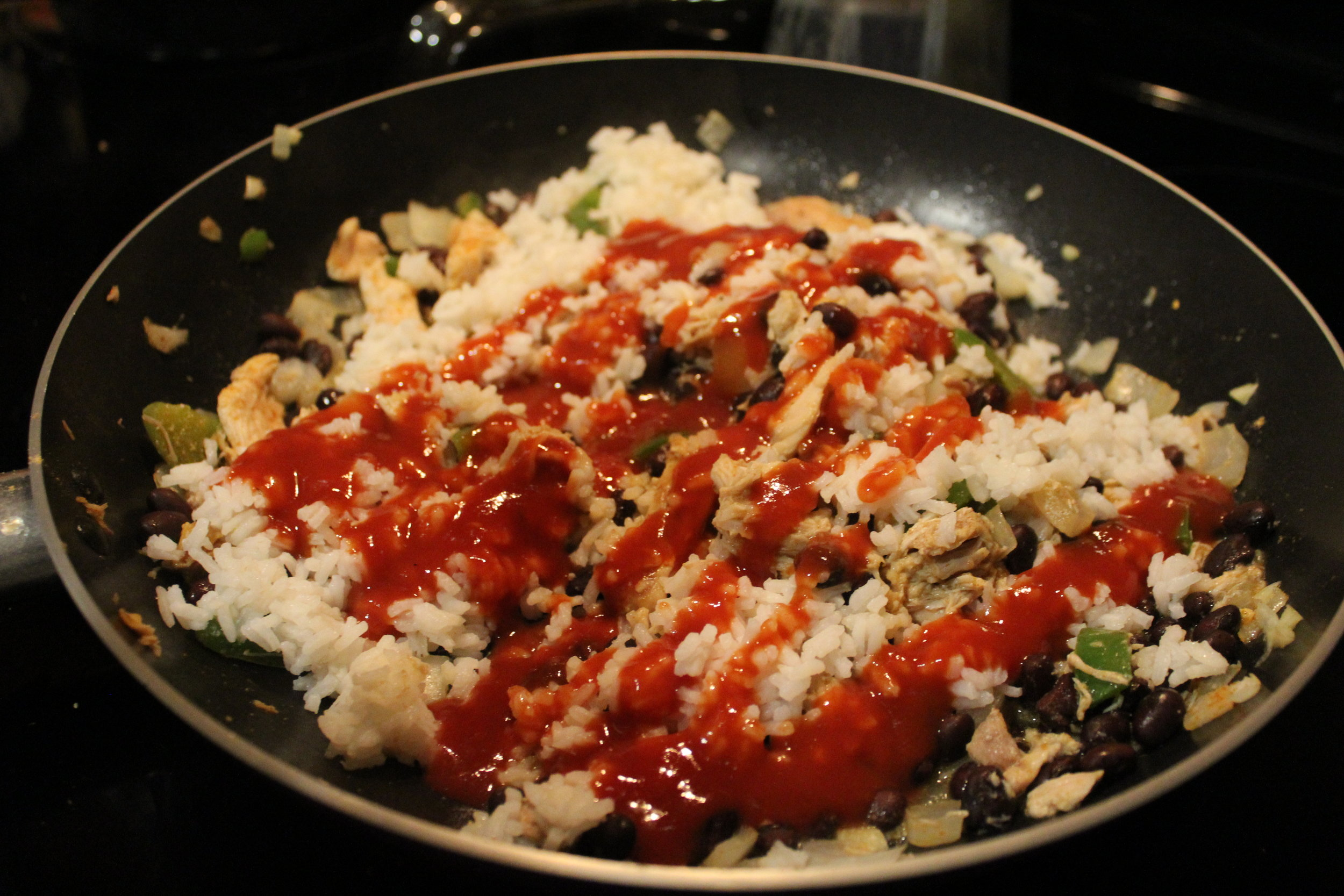 Add in the rice, beans, & sauce. I usually let this cover and simmer until the rice is cooked (of course I use the 5 minute quick rice), this lets the flavors blend together. Ethan loves him some taco sauce - there's never enough.