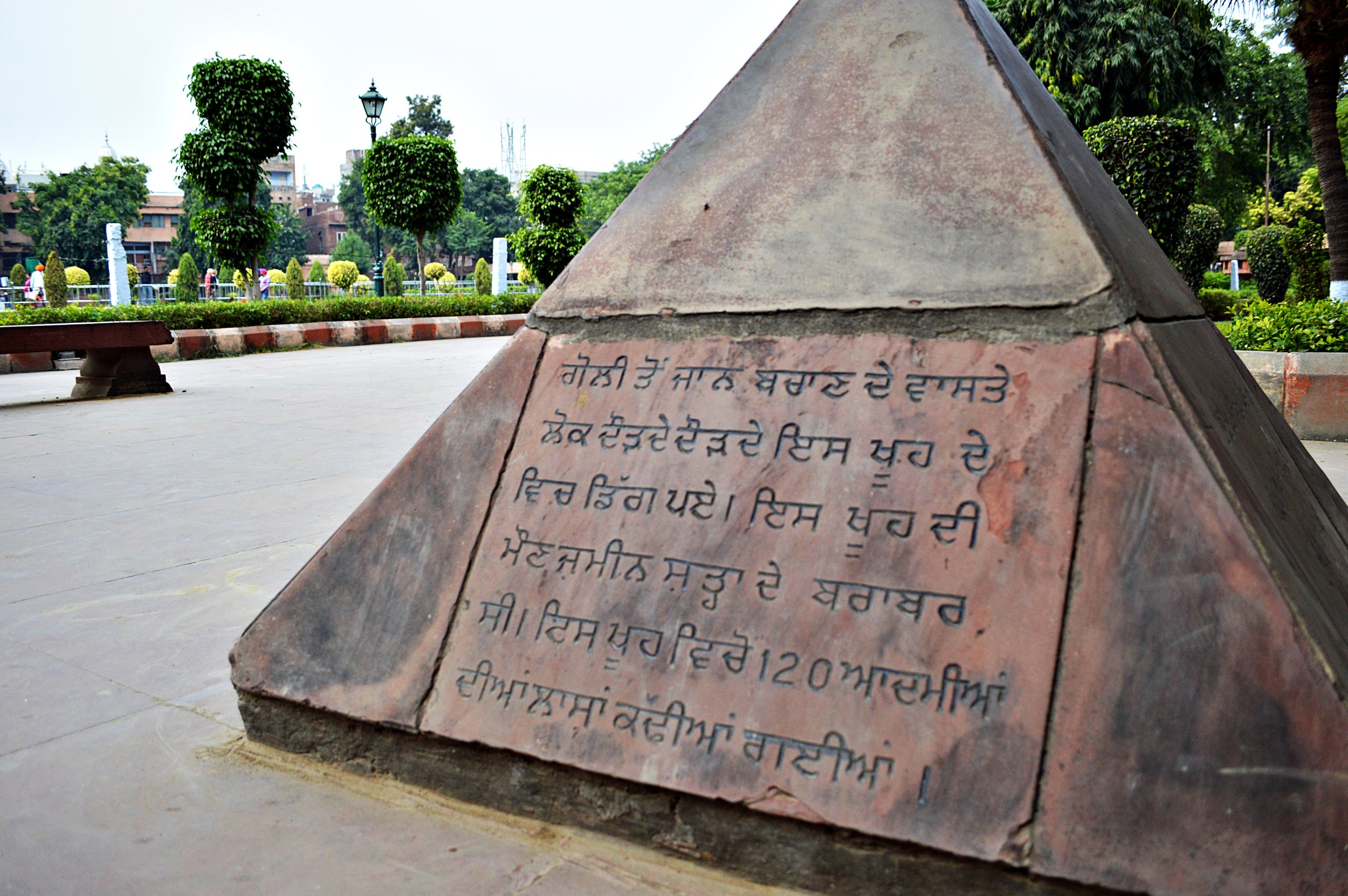 Sign at Jallianwala Bagh describing how at least 120 people jumped to their death in a well instead of being shot during an unprecedented attack by the ruling British. Amritsar, Punjab.