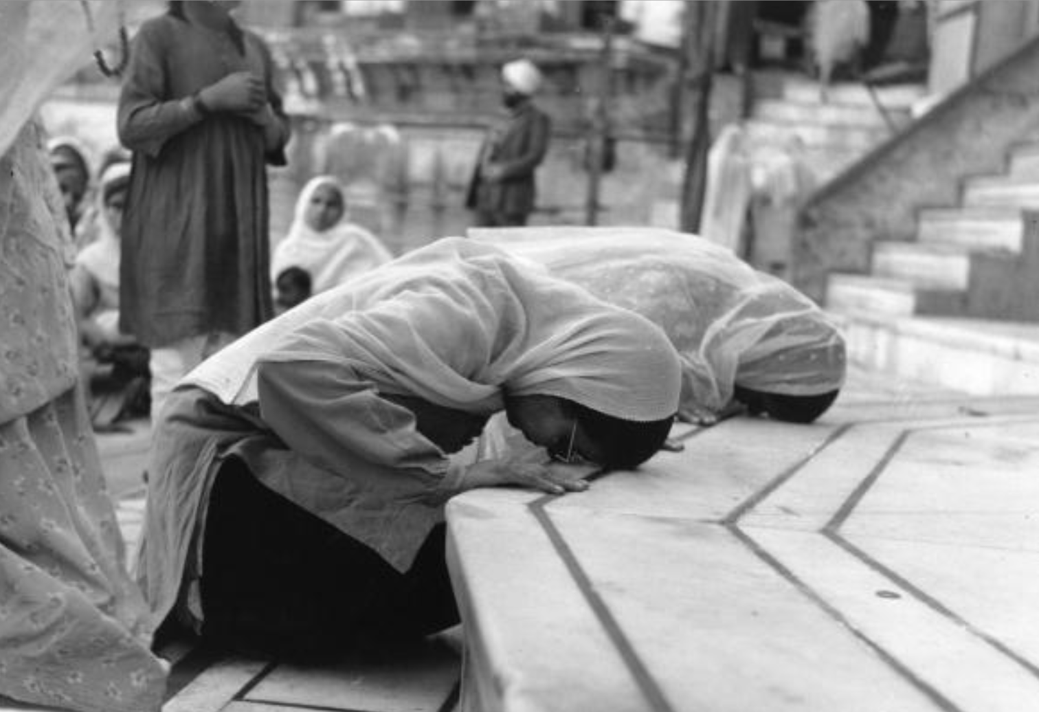 Circa 1955: two Sikh women bow outside the entrance to Darbar Sahib, which is one of the most historically significant gurdwaras for Sikhs, and is located in Amritsar, Punjab. (Photo by Three Lions/Getty Images)