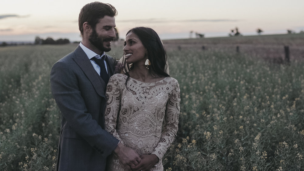 Newly married couple standing in a field at sunset in their wedding video