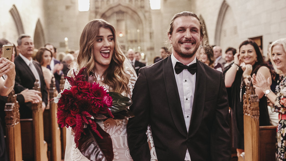 Newly married couple smiling walking down the aisle after their wedding ceremony