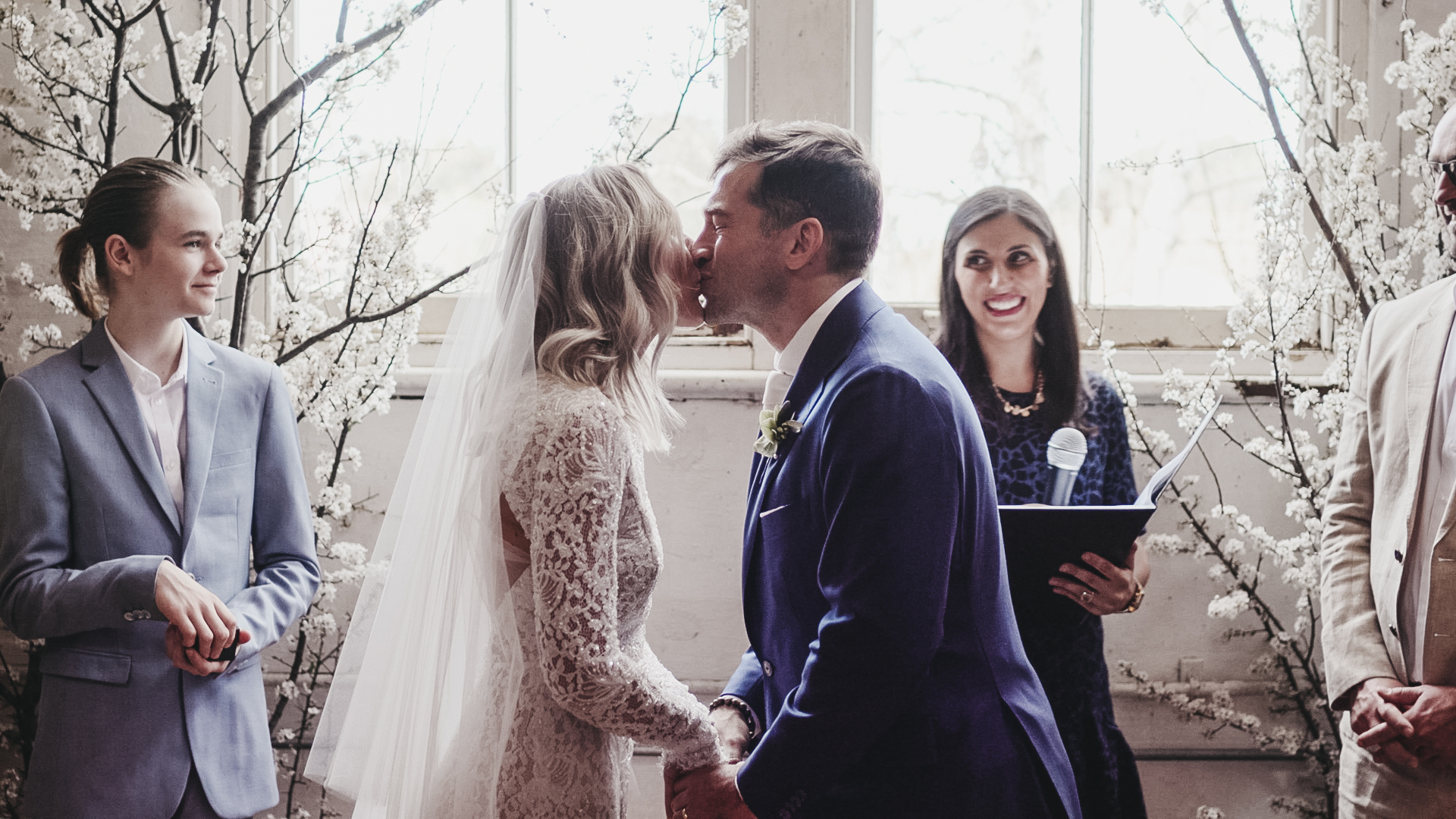 Newly married couple sharing their first kiss as husband and wife at their rustic country wedding