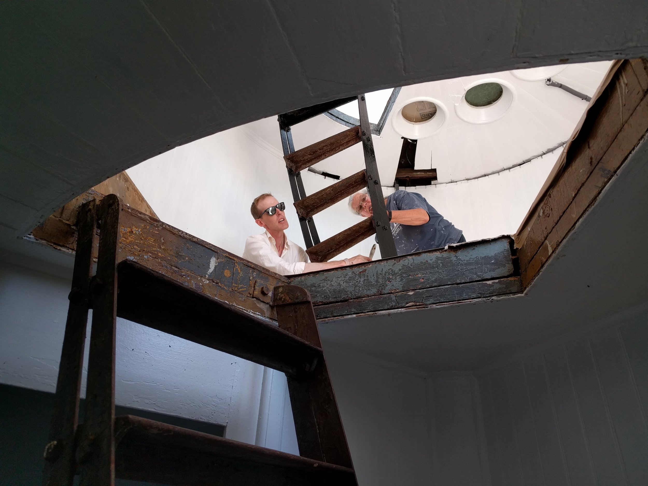 Eileen and Stefan apply the first coat of black paint to the ladder from the Watch Gallery to the Lantern Gallery.