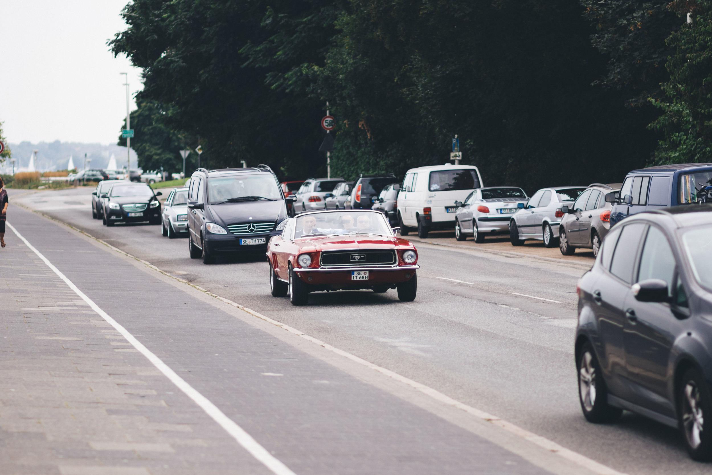 Ein Roter Mustang Oldtimer fährt über die Kiellinie bei der Seebar Kiel - Seebad Düsternbrook. Im roten Mustang Oldtimer sitzen 3 Männer, einer davon ist der Bräutigam. Das Foto ist während einem Fotoshooting in Kiel von Hochzeitsfotograf Phil Schreyer 2016 entstanden.