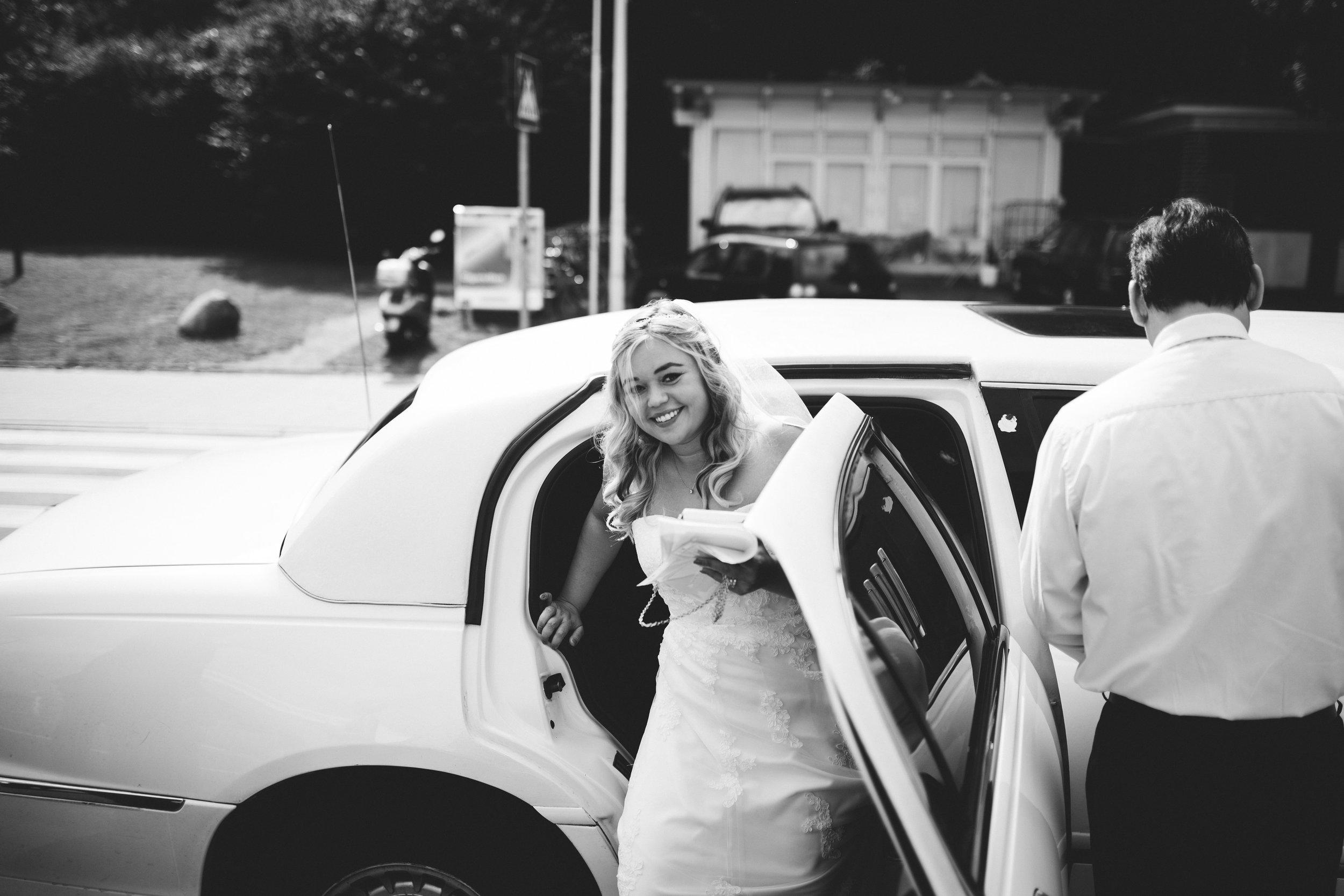 Eine Braut steigt aus einer Strechlimousine an der Kiellinie vor der Seebar Kiel auf dem weg zu Ihrer Hochzeit. Die Braut lacht in die Kamera und das Bild ist schwarz weiß. Diese Momemntaufnahme hat Hochzeitsfotograf Phil Schreyer geschossen