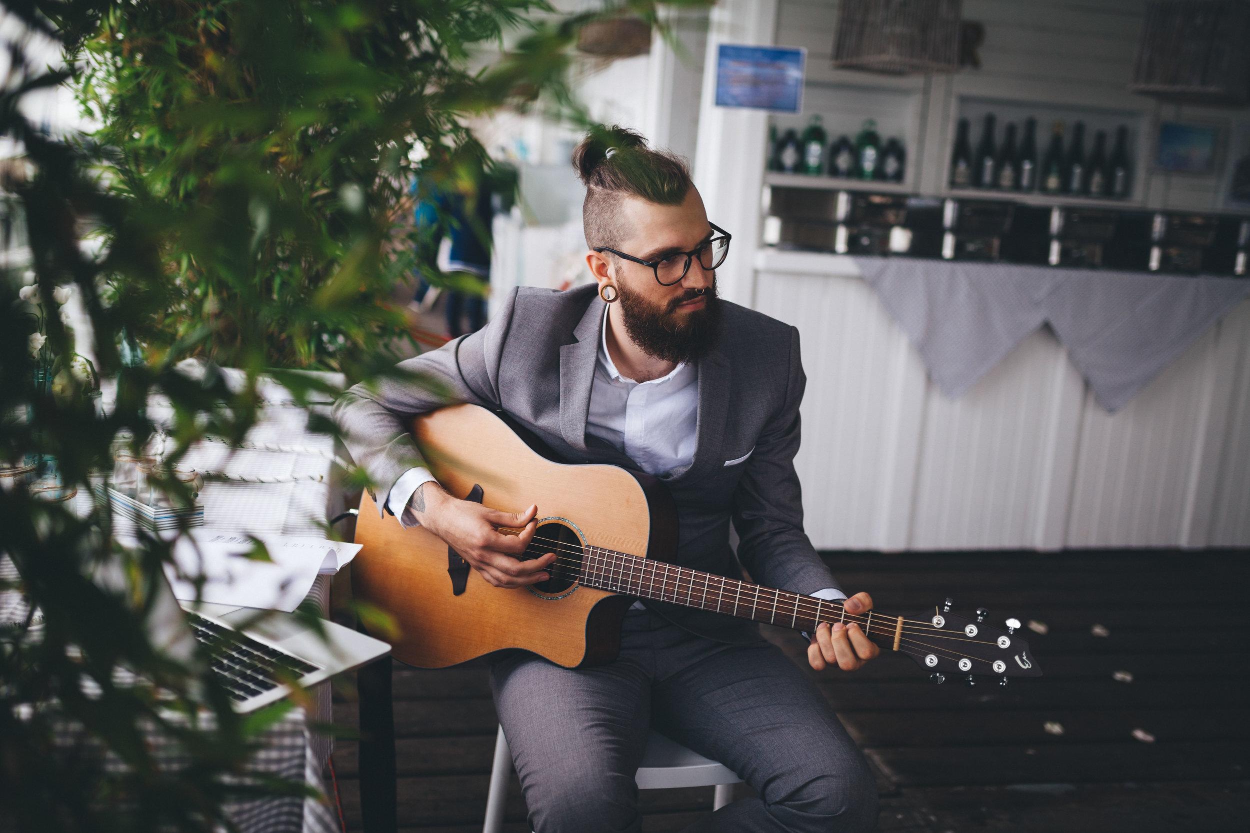Bärtiger Gitarrist mit Brille spielt bei einer Hochzeit in der Seebar Kiel Gitarre. Das Foto ist bei einer Hochzeit in Kiel von Phil Schreyer entstanden.