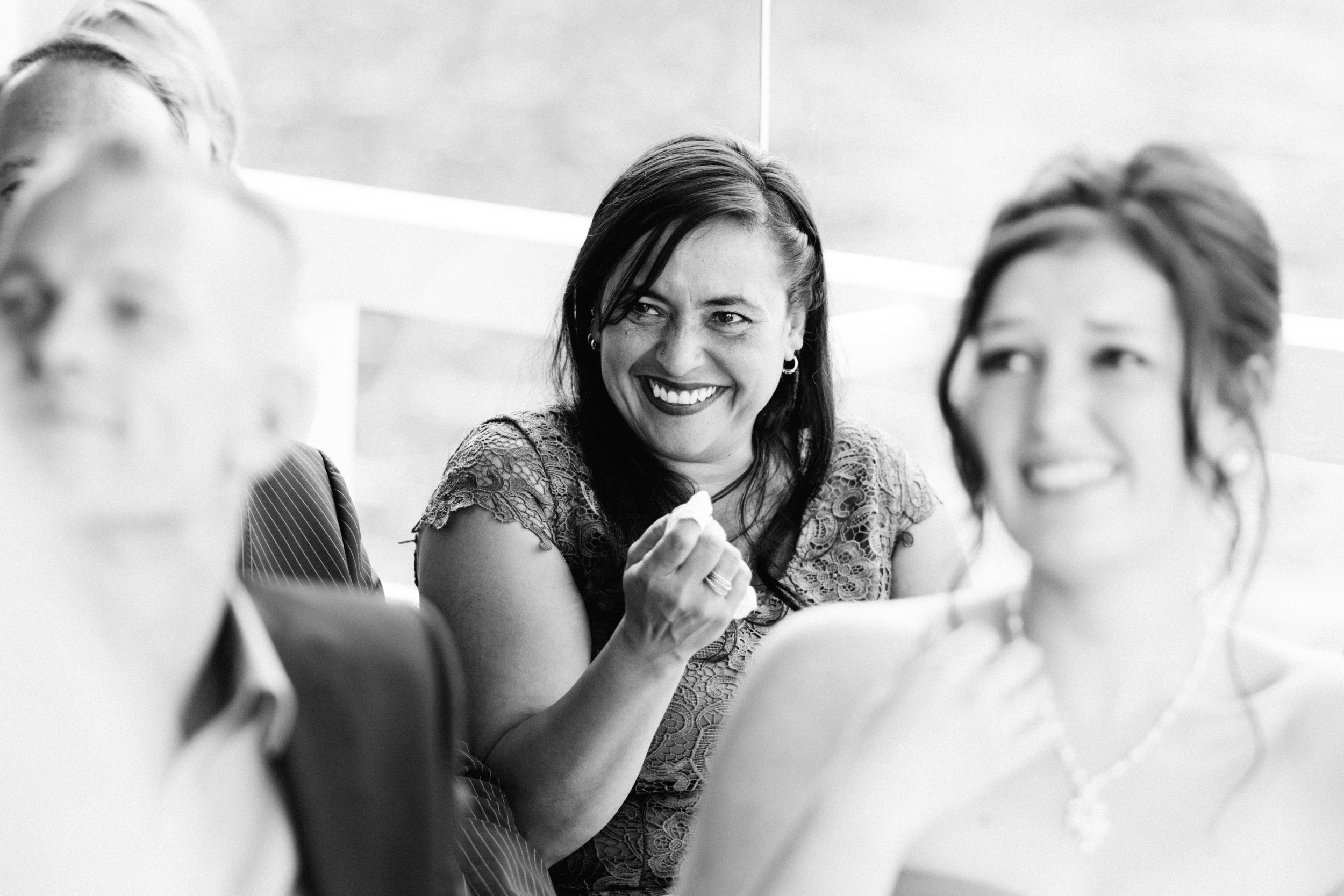 Eine Frau lacht mit Tränen in den Augen auf einer Hochzeit in Kiel an der Förde. Die Aufnahme ist in Schwarz Weiß und von Hochzeitsfotograf Phil Schreyer geschossen.