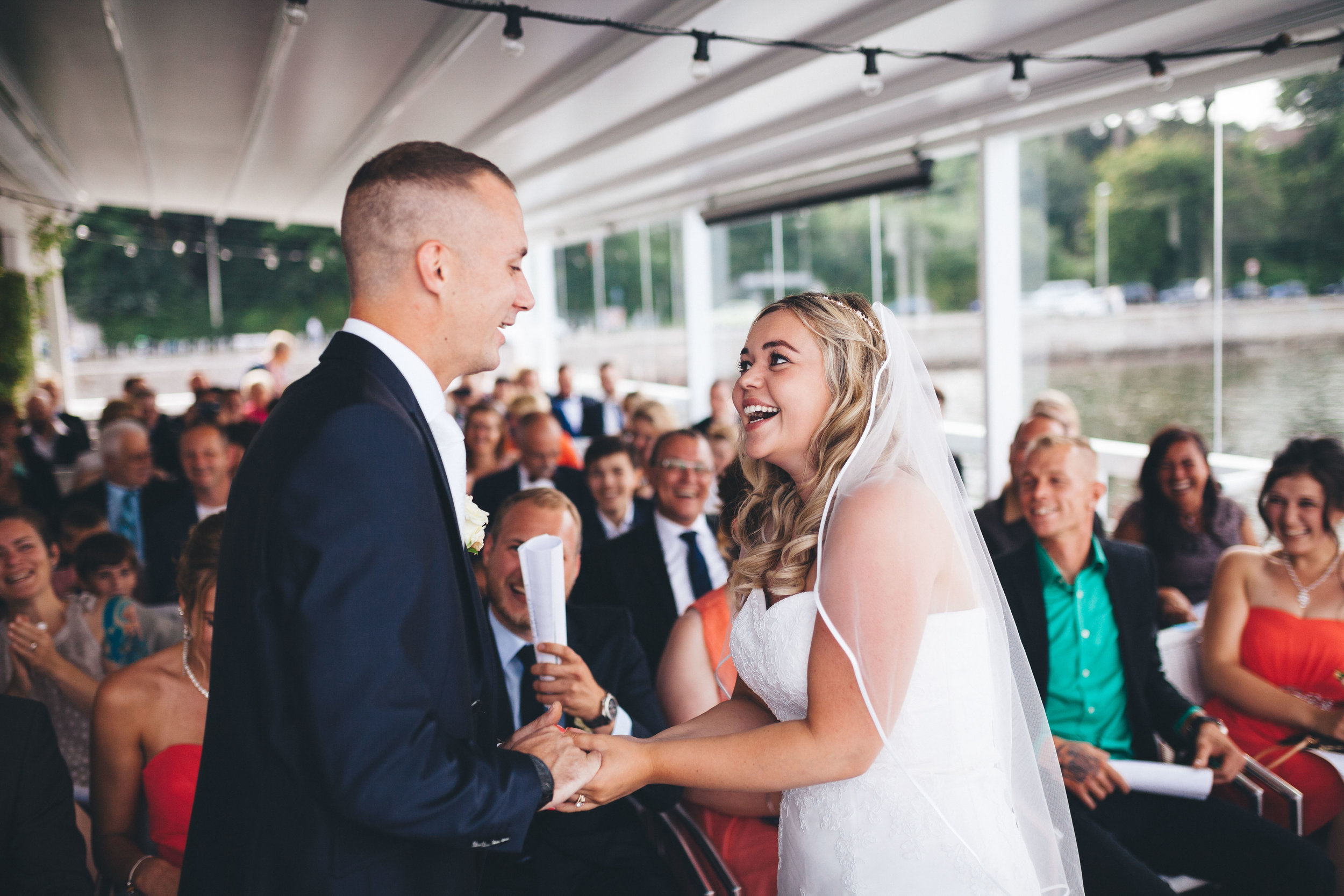 Braut und Bräutigam halten sich bei einer Hochzeit die Hände, schauen sich an und lachen. Sie sind energisch. Im Hintergrund sieht man die Hochzeitsgäste in der Seebar Kiel.