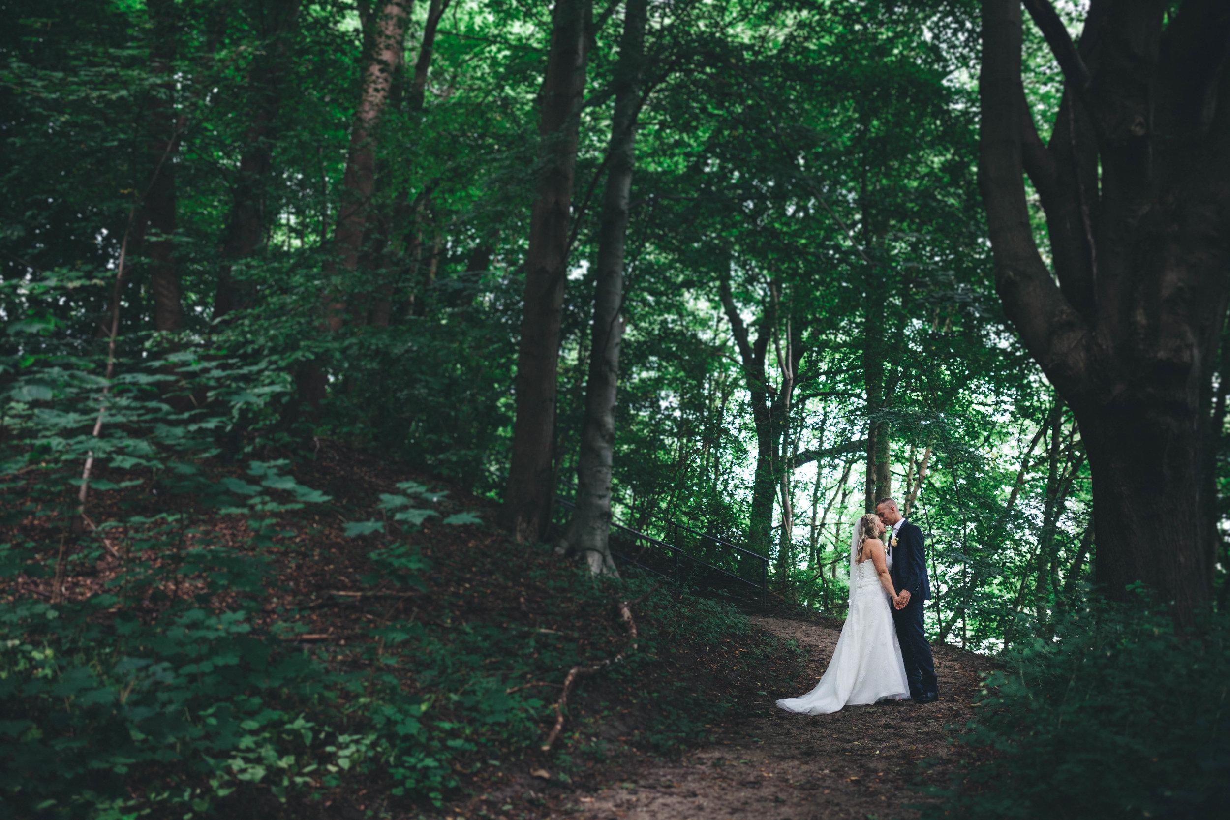 Ein hochzeitspaar steht in einem Wald mit großen Bäumen. Die halten sich fest und küssen sich. Das Portrait wurde während einer Hochzeit in der Seebar Kiel aufgenommen.