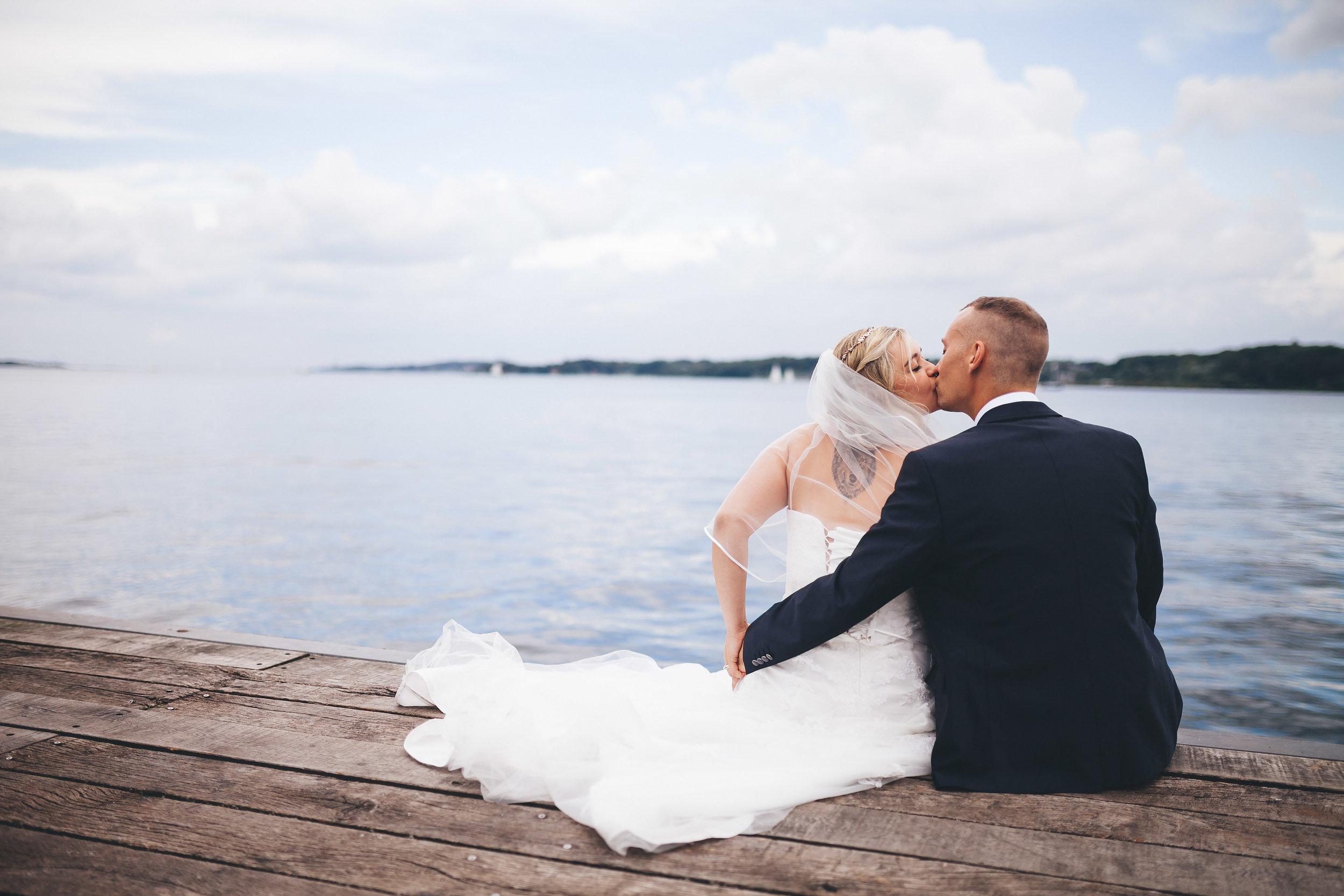 Ein Hochzeitspaar gibt sich auf einem Steg in der Seebar Kiel ein Kuss. Sie sitzen am Ende vom Steg. Die Momentaufnahme ist von Hochzeitsfotograf Kiel Phil Schreyer entstanden.