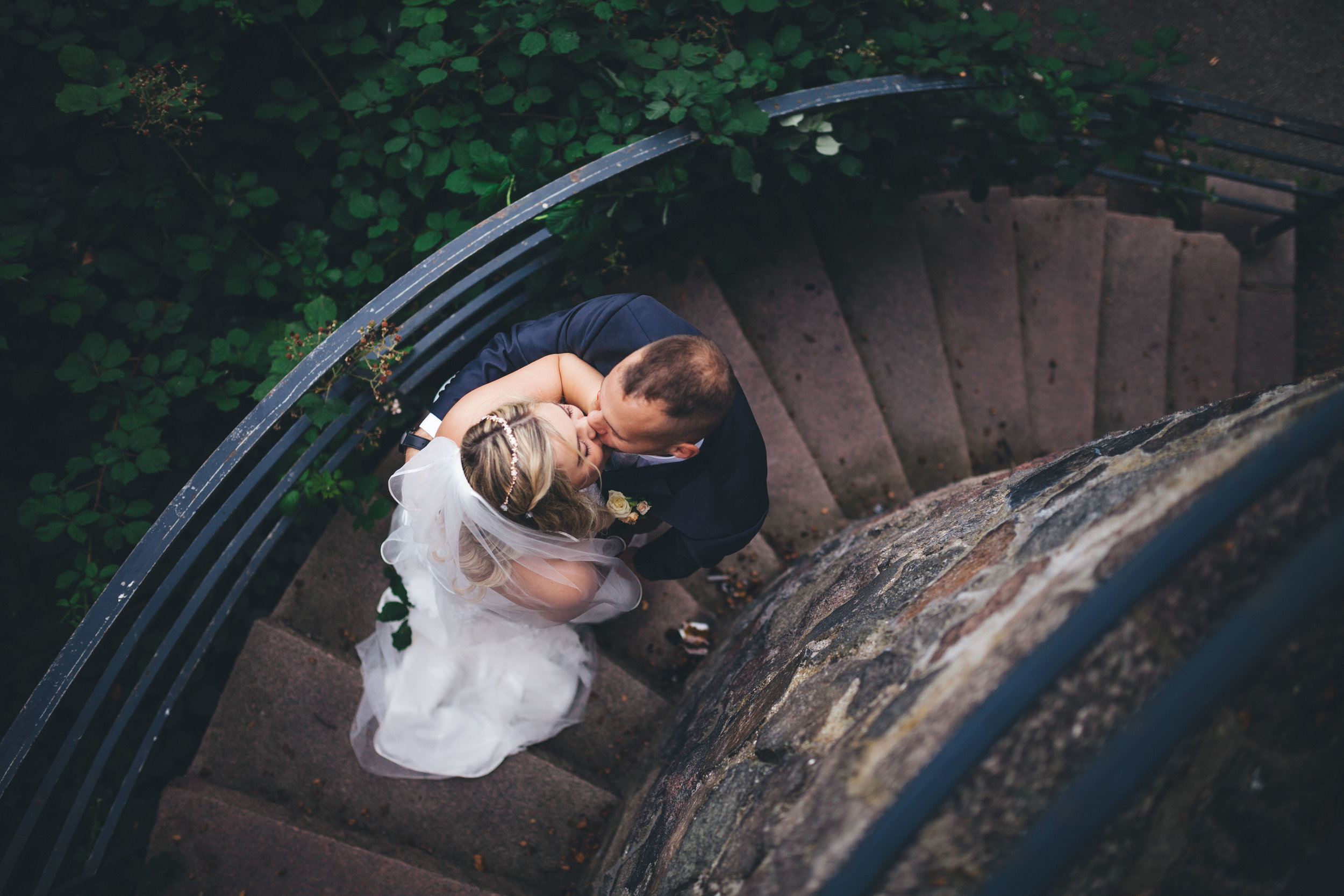 Ein Hochzeitspaar gibt sich auf einer Wendetreppe im Wald einen Kuss. Fotografiert von Oben bei einer Hochzeit von Phil Schreyer