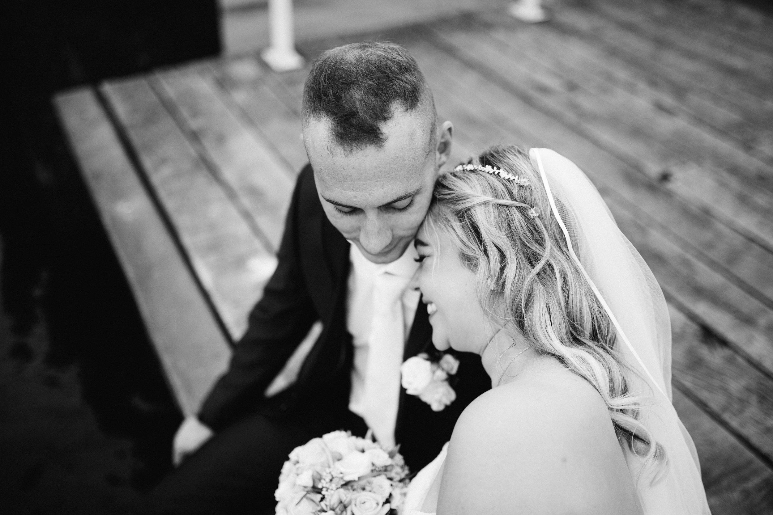 Eine Portraitaufnahme von einem Hochzeitspaar in Schwarz Weiß. Sie lehnt sich an seine Schulter und beide sind in ihrer eigenen Welt versunken. Die Aufnahme ist bei einer Hochzeit in Kiel entstanden.