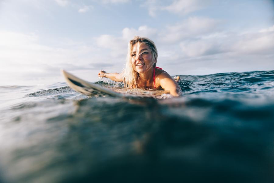 Josi paddelt auf ihrem Surfboard der Sonne entgegen