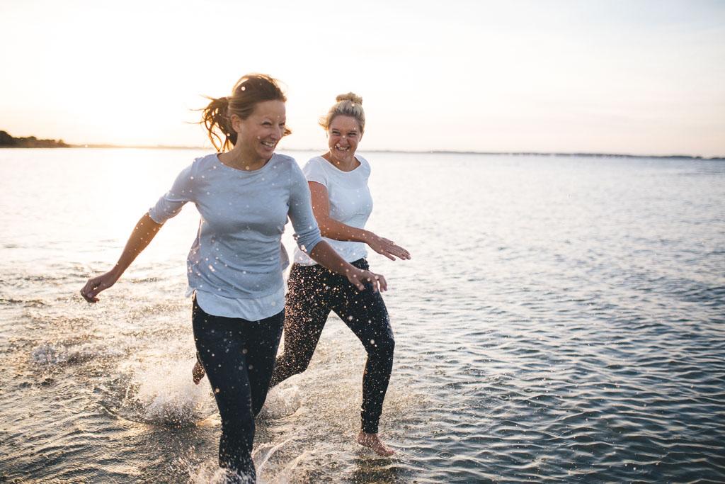 zwei freundinen laufen am Strand im Ortsteil Stein von Kiel, durchs Wasser. Im Hintergrund geht die Sonne unter. Das Foto entstand bei einem Freundinen Fotoshooting in Kiel von Fotograf Phil Schreyer.